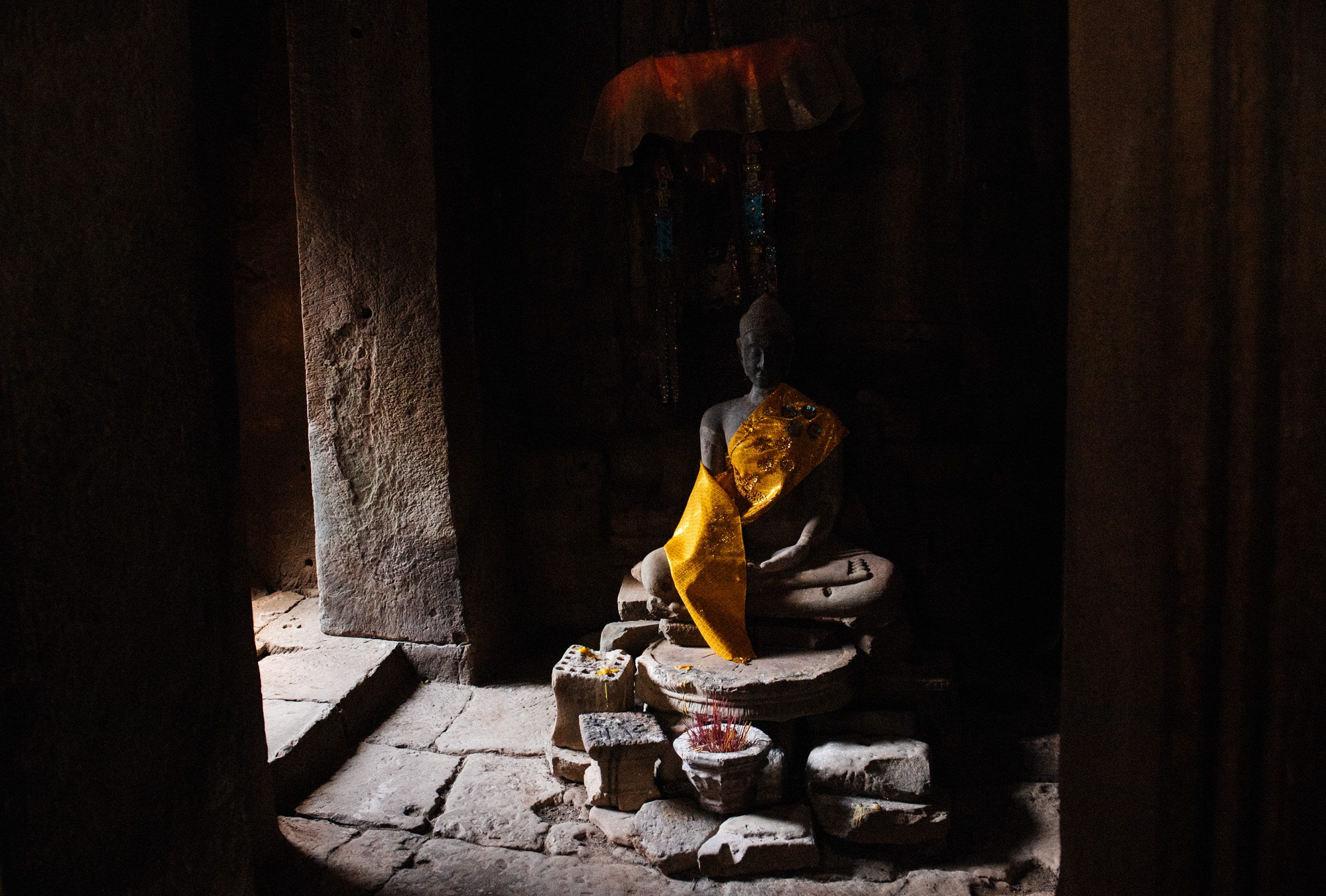 A statue of Buddha sits in a dark corner with several sticks of incense burning at its feet.