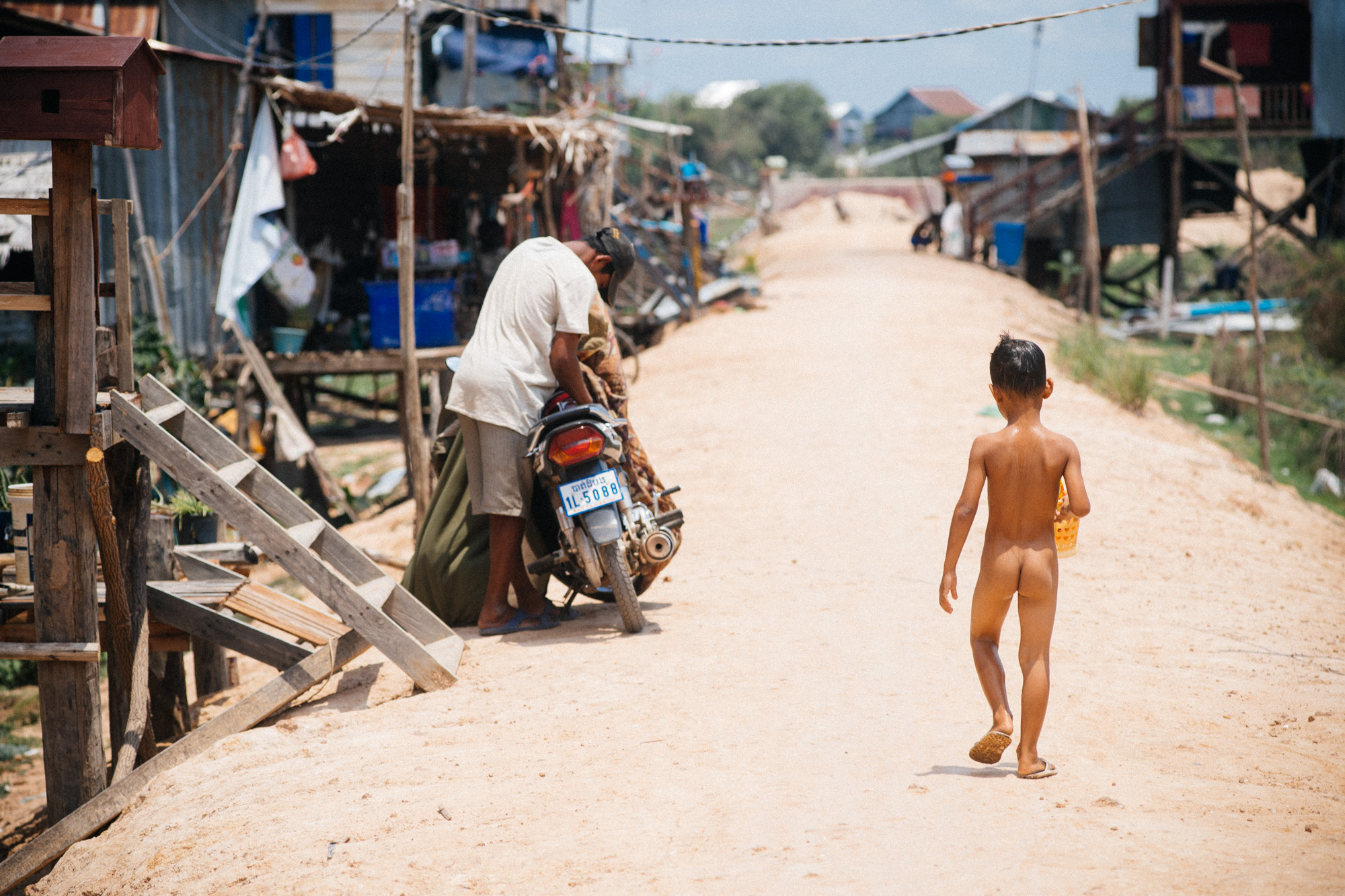 After cooling himself off with a hose in the hot 35˚C, a boy walks back home. Children often run around completely naked in the countryside of Cambodia.