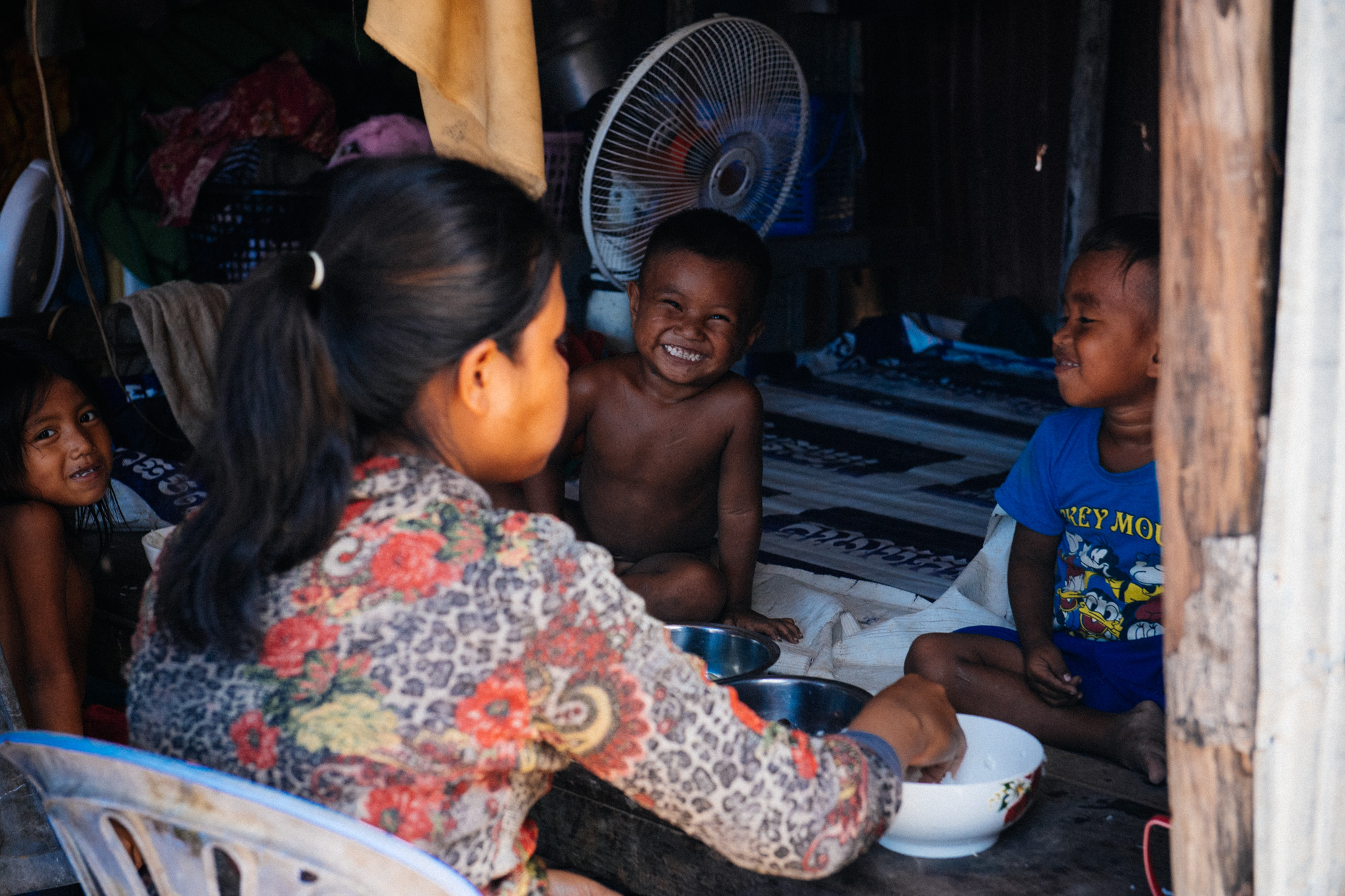 Three kids have lunch with their caretaker. The most instinctive reaction of the little boys was to laugh so hard and wave to the camera as soon as he noticed our presence.