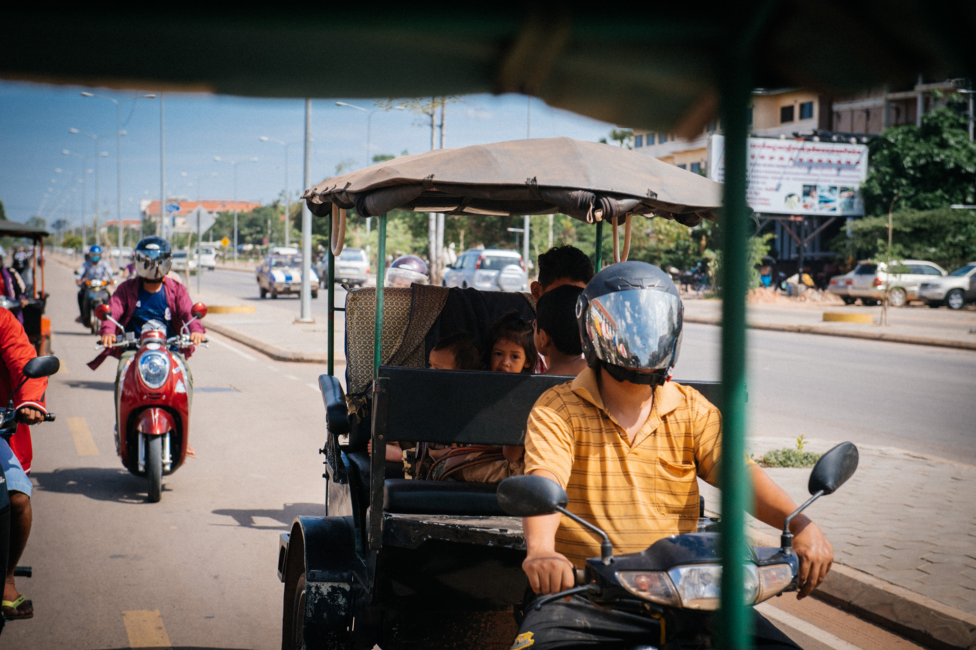 Children accompany their father on a tuk-tuk ride. These adapted motorcycles are an essential mean of transportation in Southeast Asian countries, cheaper than cars and more convenient than bikes.