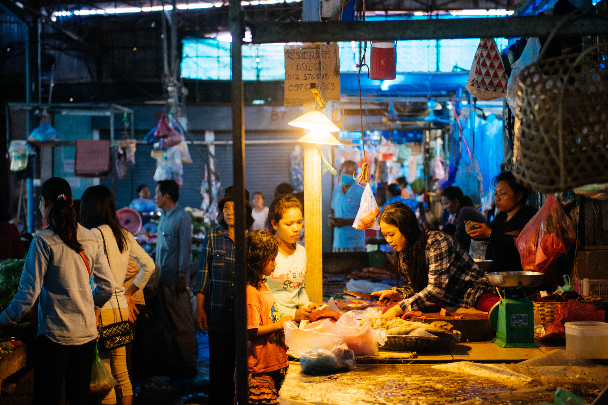 Sitting on the same platform she cuts meat on, woman selects produce to sell to customers.