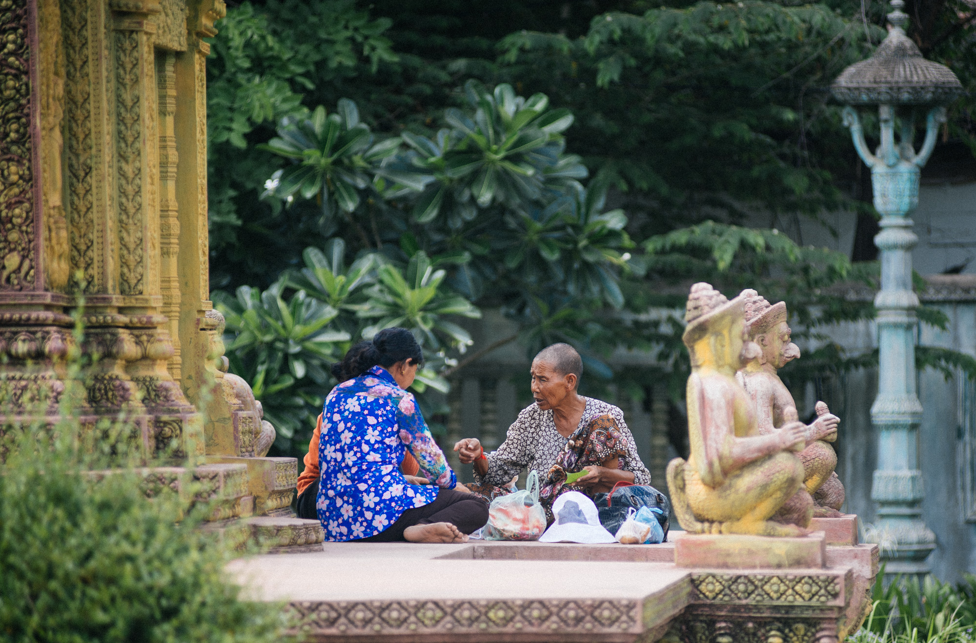 Women sit down for a meal at the monument built for the victims during the Cambodian civil war.