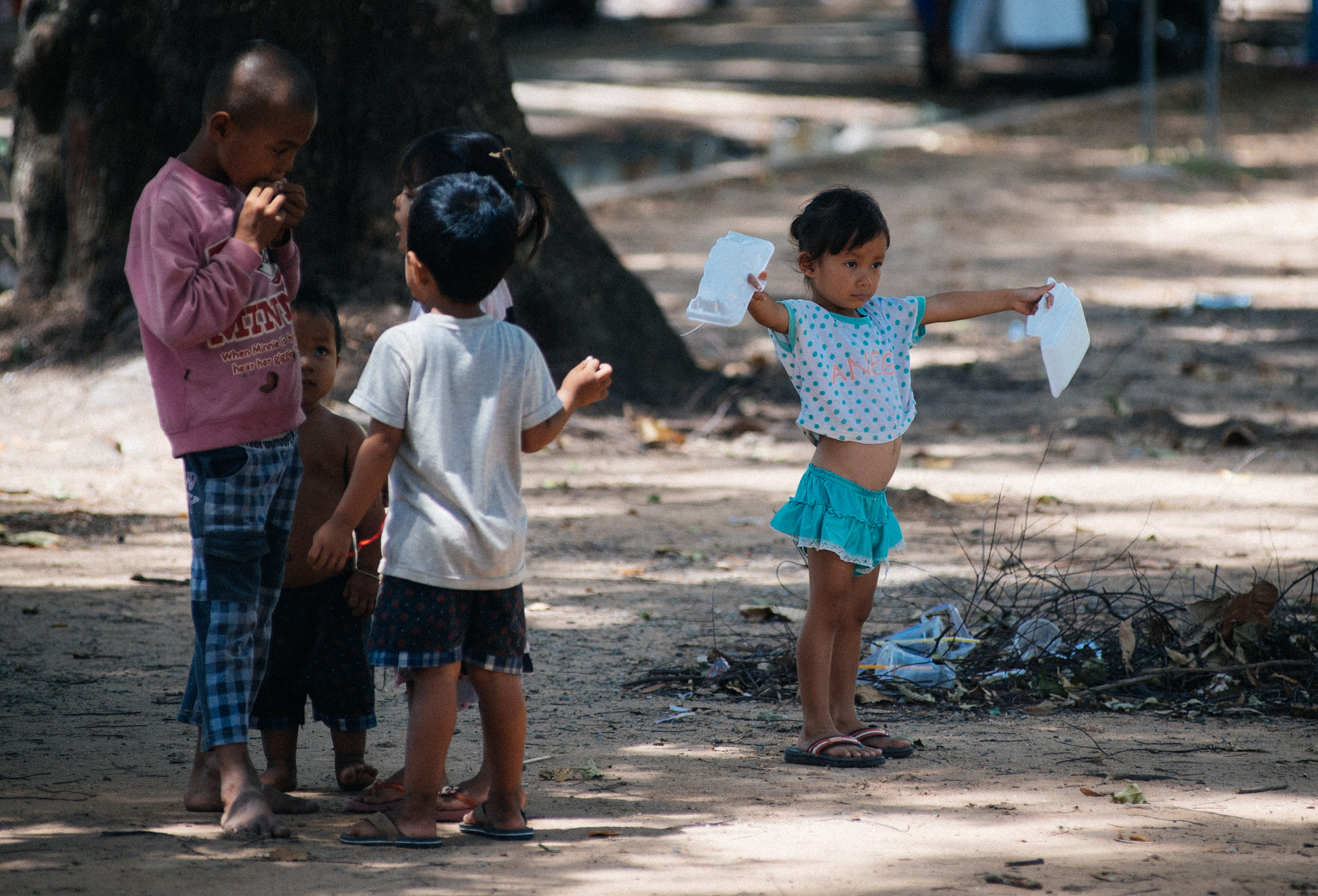 At a park in front of the Royal Family's Siem Reap house, a group of kids plays under trees full of fruit bats.