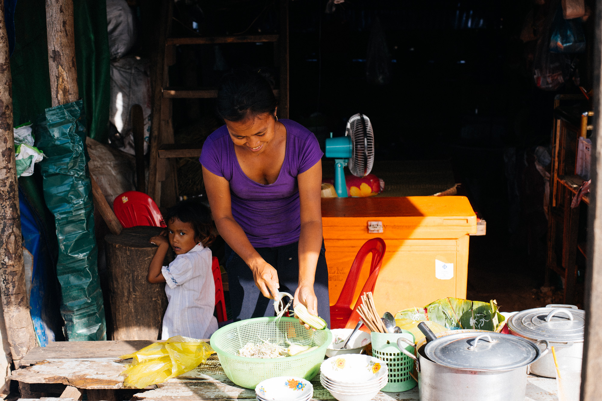 Girl hides behind woman cooking food to sell. Some people would stop by on their scooters to buy food and take home.