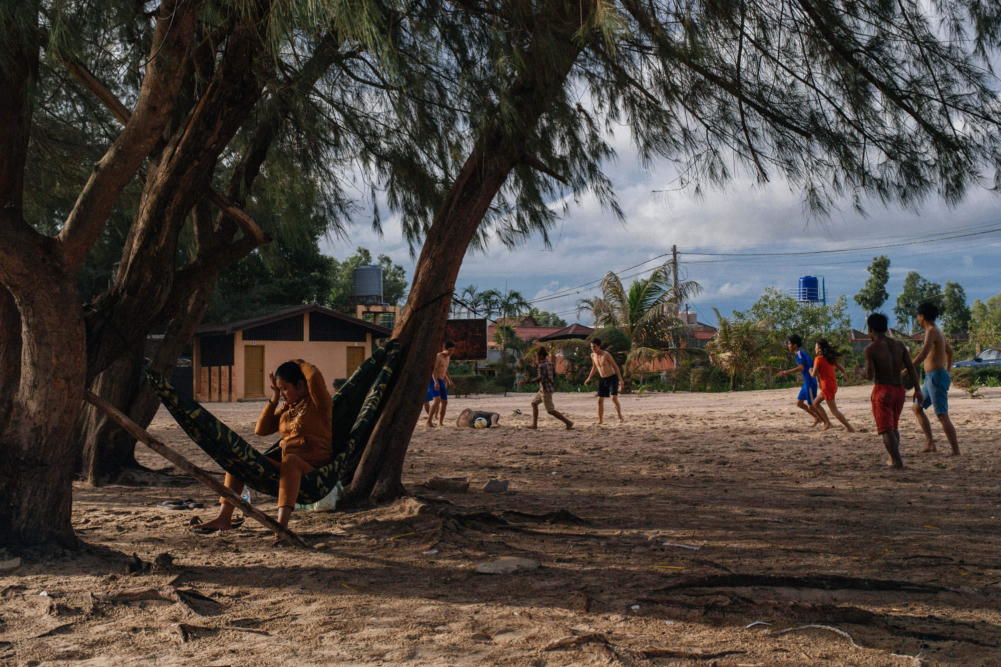 A group of teenagers play football and barbecue seafood on the sand.