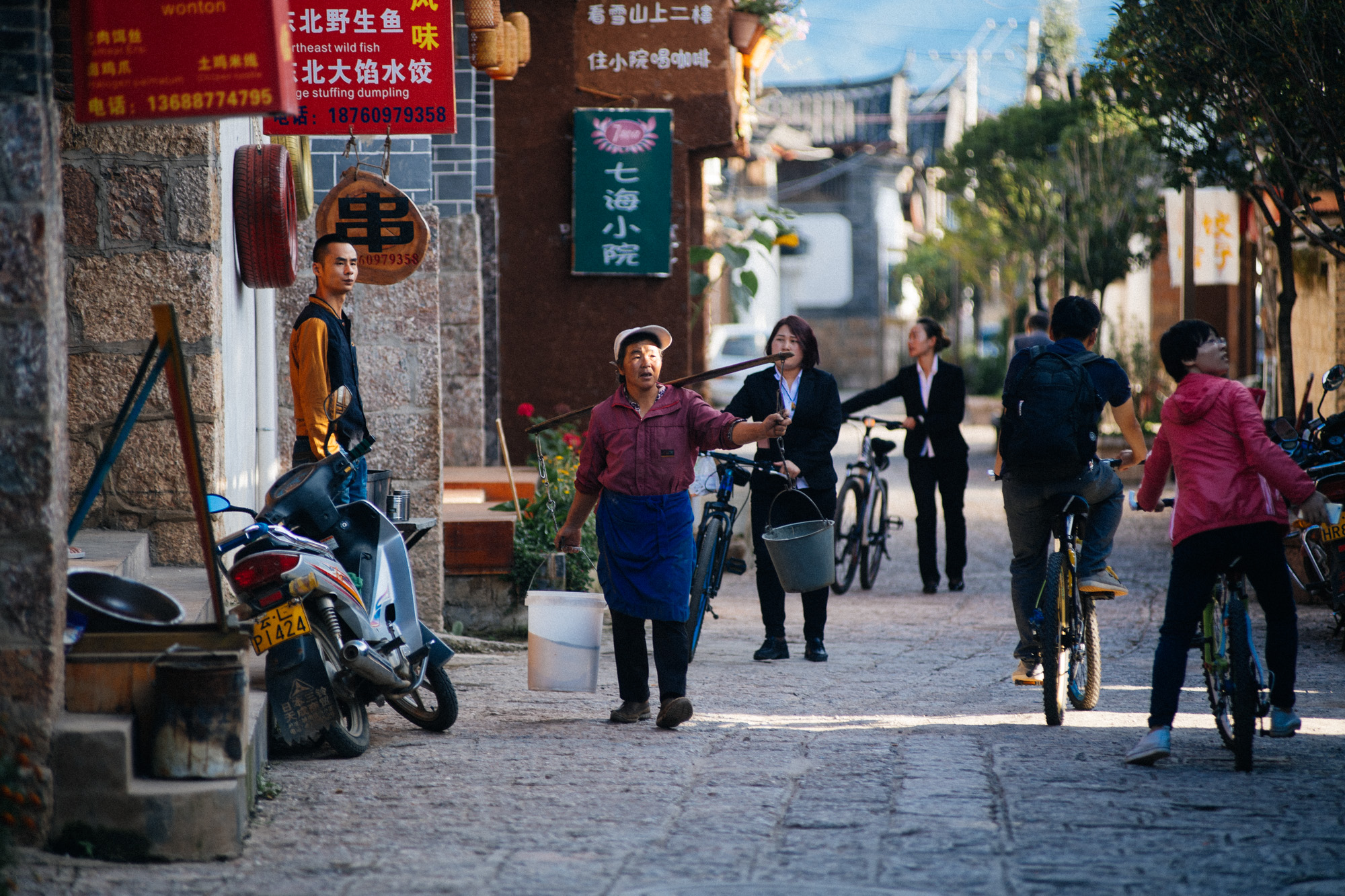 Woman carries two buckets of water while two other women, dressed in a more modern fashion, head back to work, most likely at the restaurants close to the frescoes where all the tourists are taken.