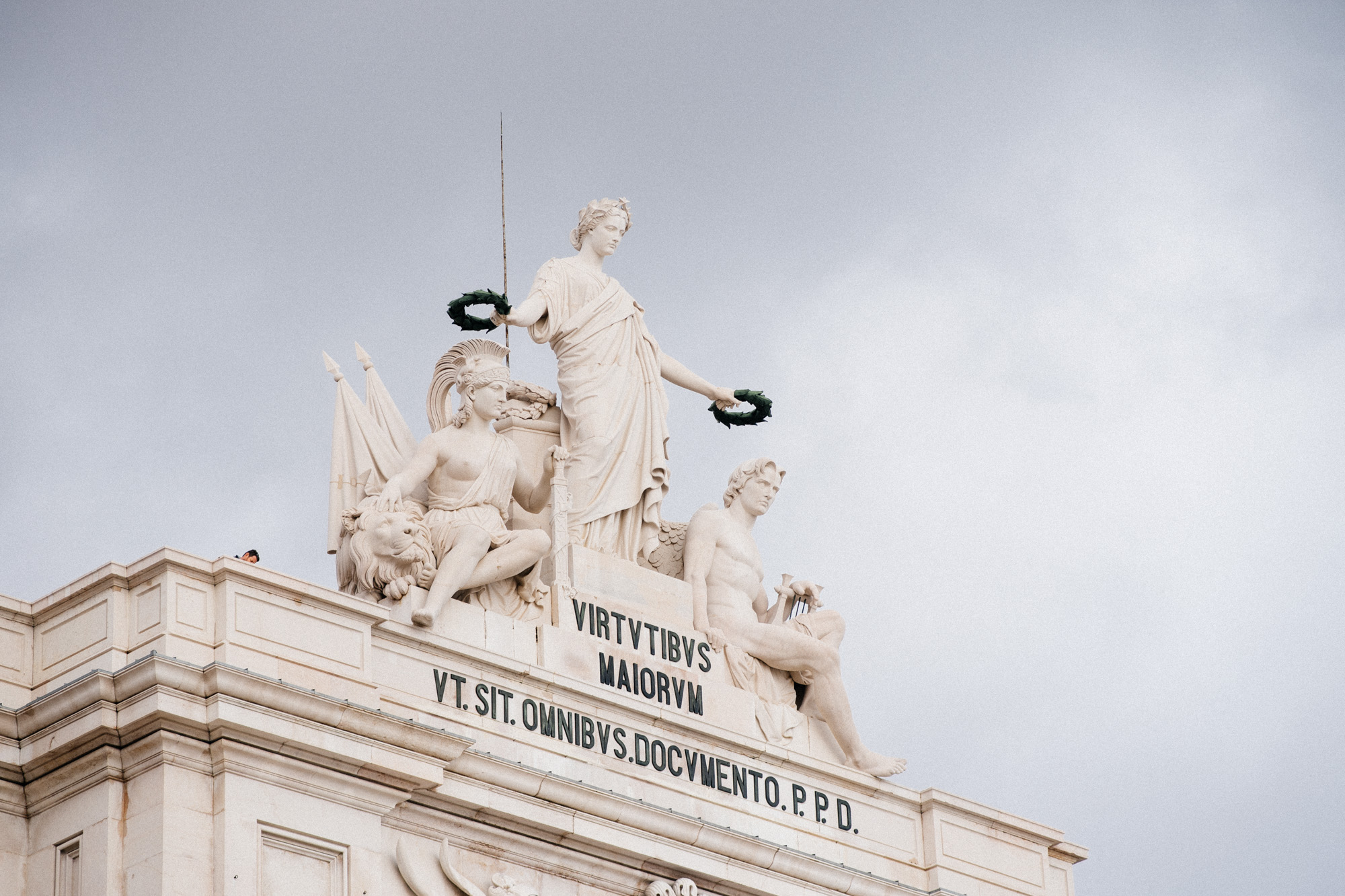 "Statues above the Arco da Rua Augusta overwatch the Praça do Comércio. The inscription reads ""Virtues of the Biggest will serve to all as a teaching. Dedicates to public expenses."""