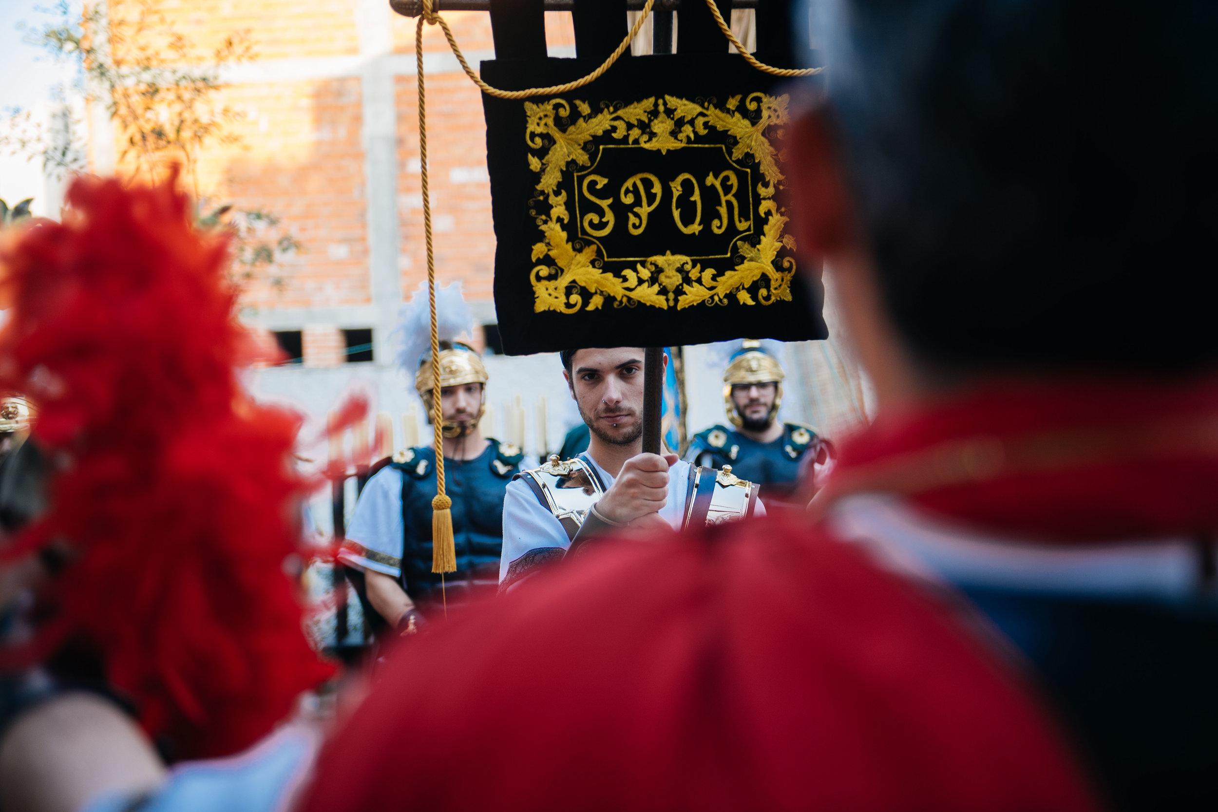 Representing Roman legionnaires, man holds banner with the initials for Senatus Populusque Romanus, the Roman senate and people.