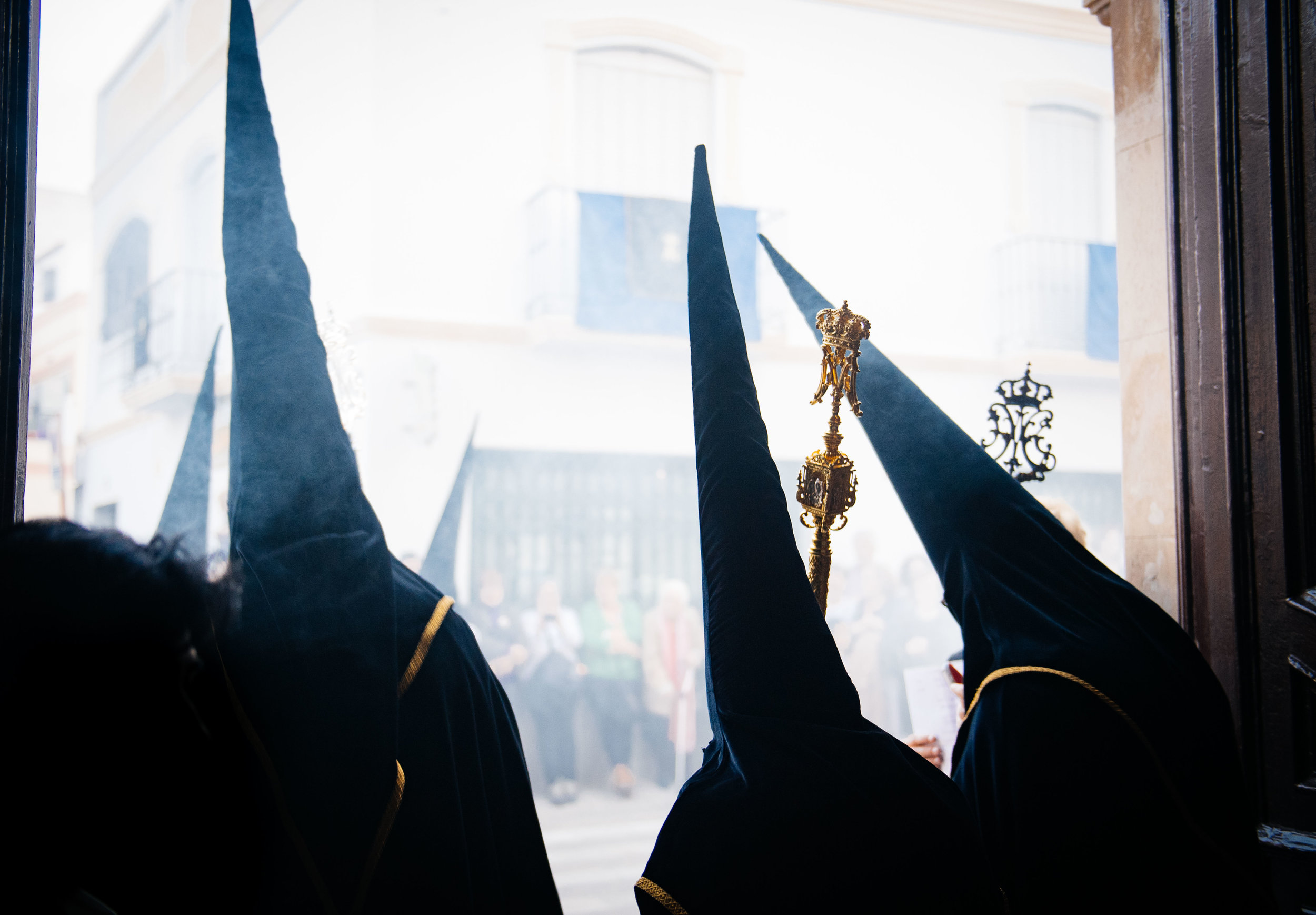 Penitents walk through the church door to meet the public and walk through the streets.