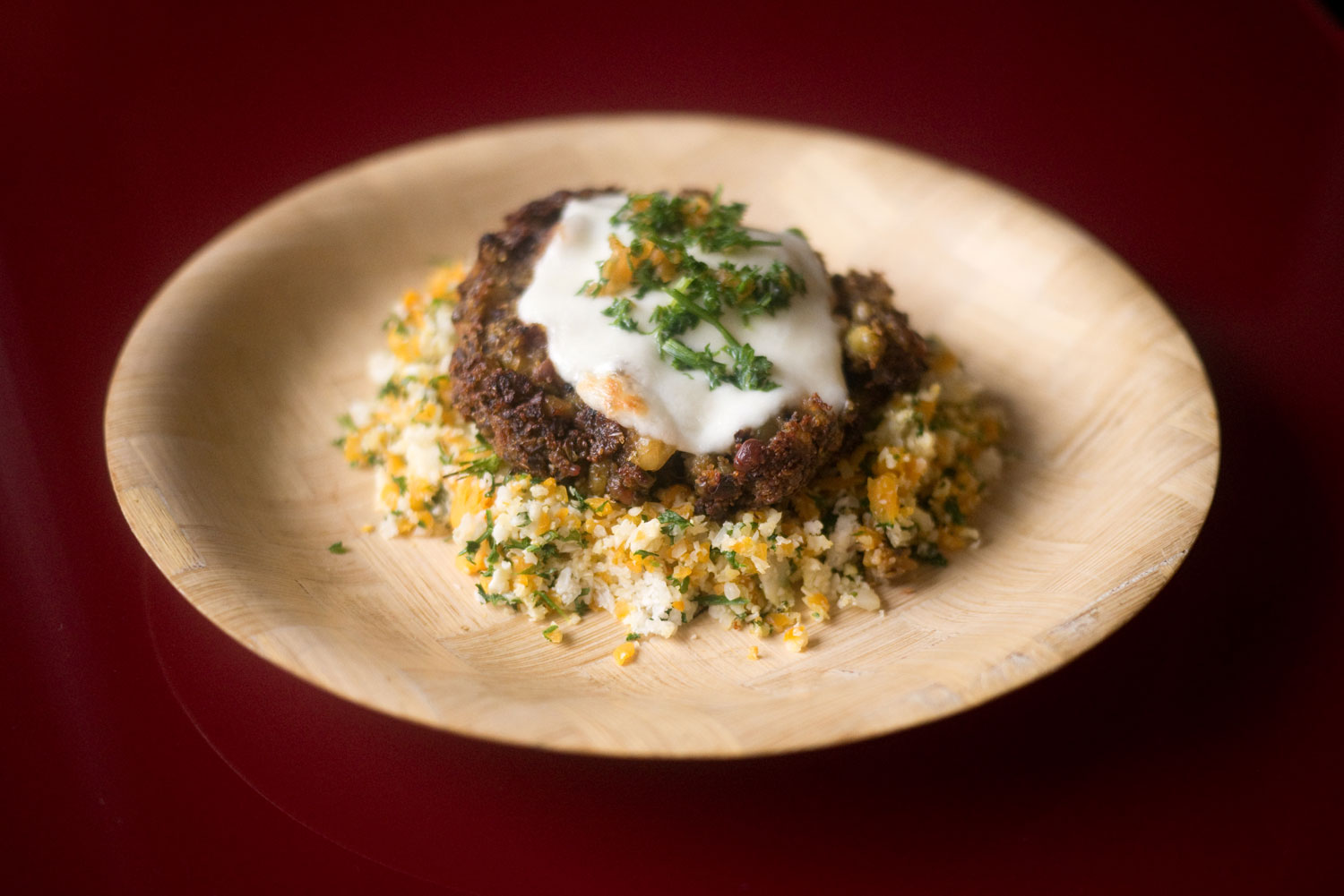Teff patty on a bed of sautéed cauliflower & pumpkin topped off with parsley and mozzarella.