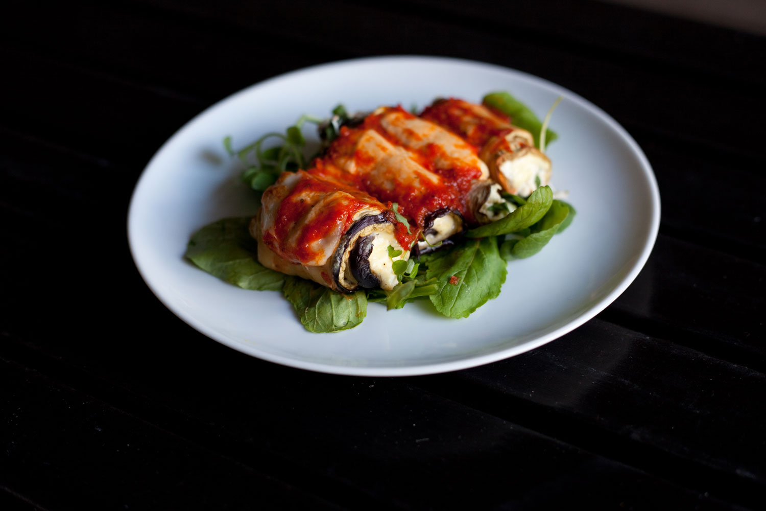 Eggplant Rolls on a bed of arugula.