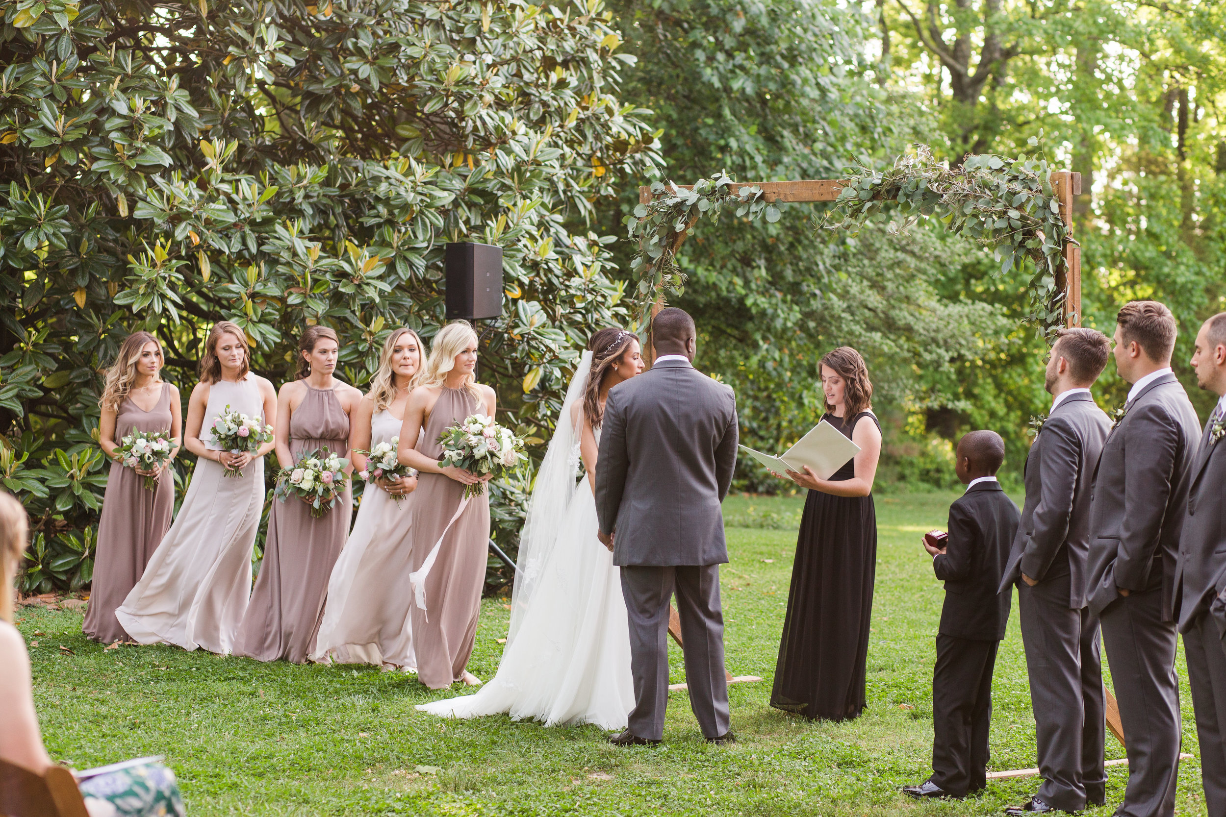 An outdoor wedding ceremony under the trees.