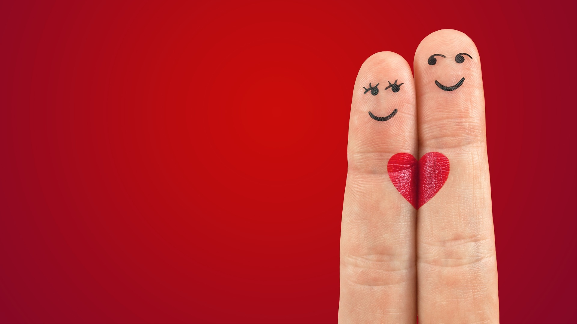 Two fingers with faces drawn on them, with a red background