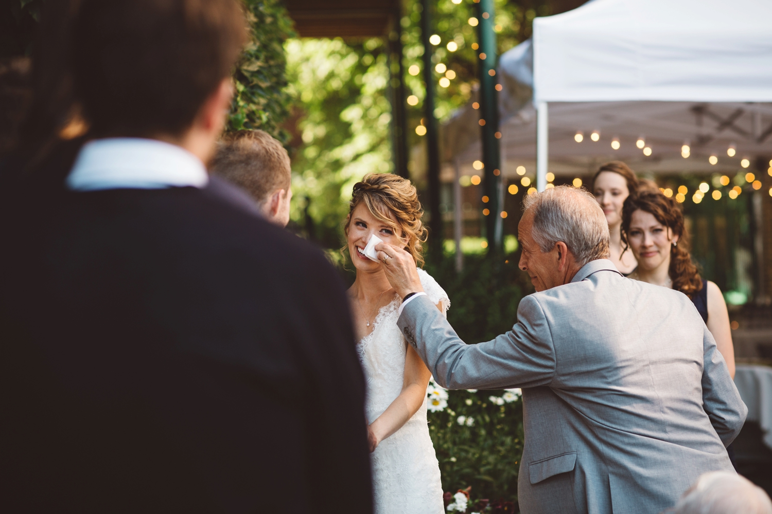dad wiping tears for bride