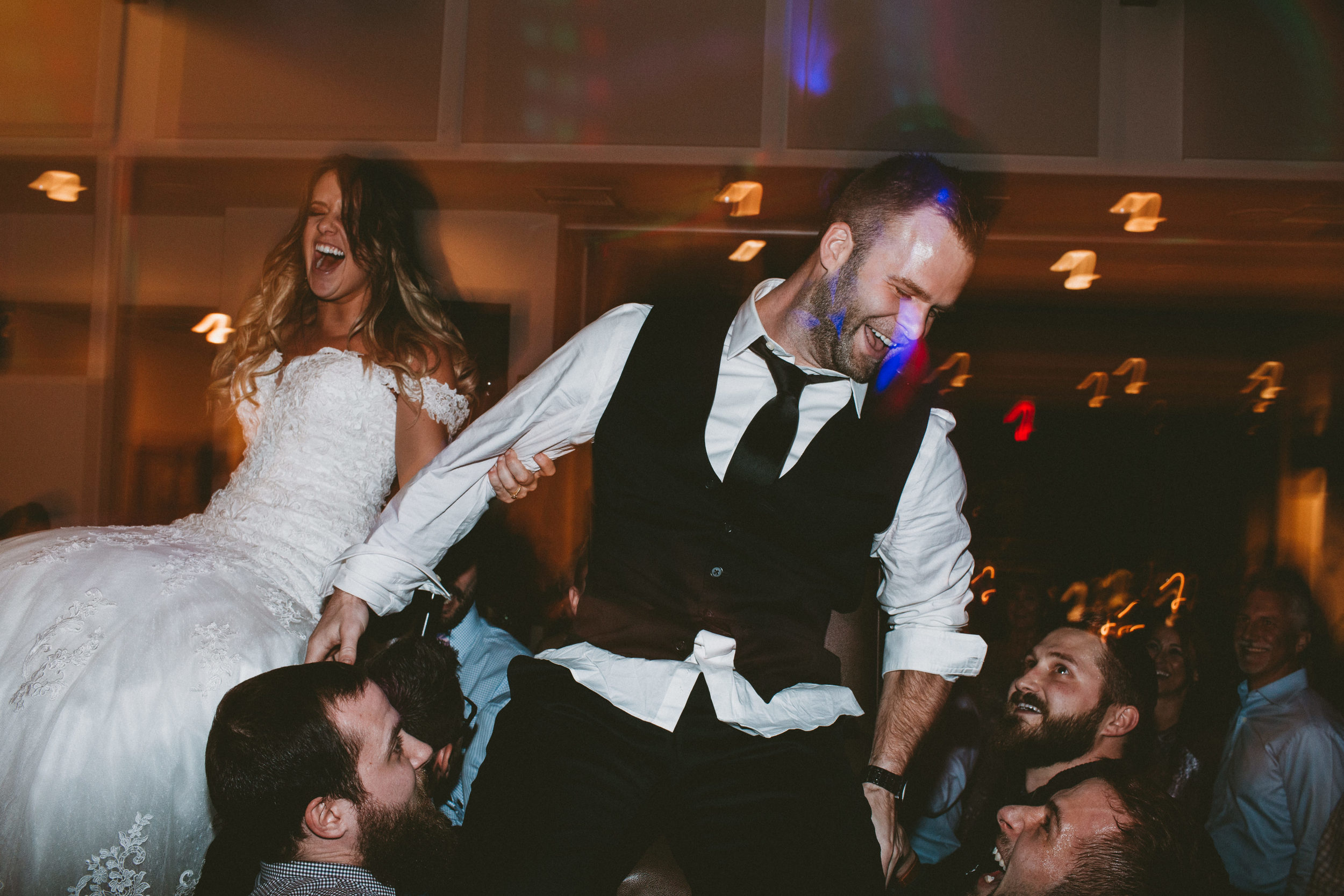 bride and groom lifted on chairs