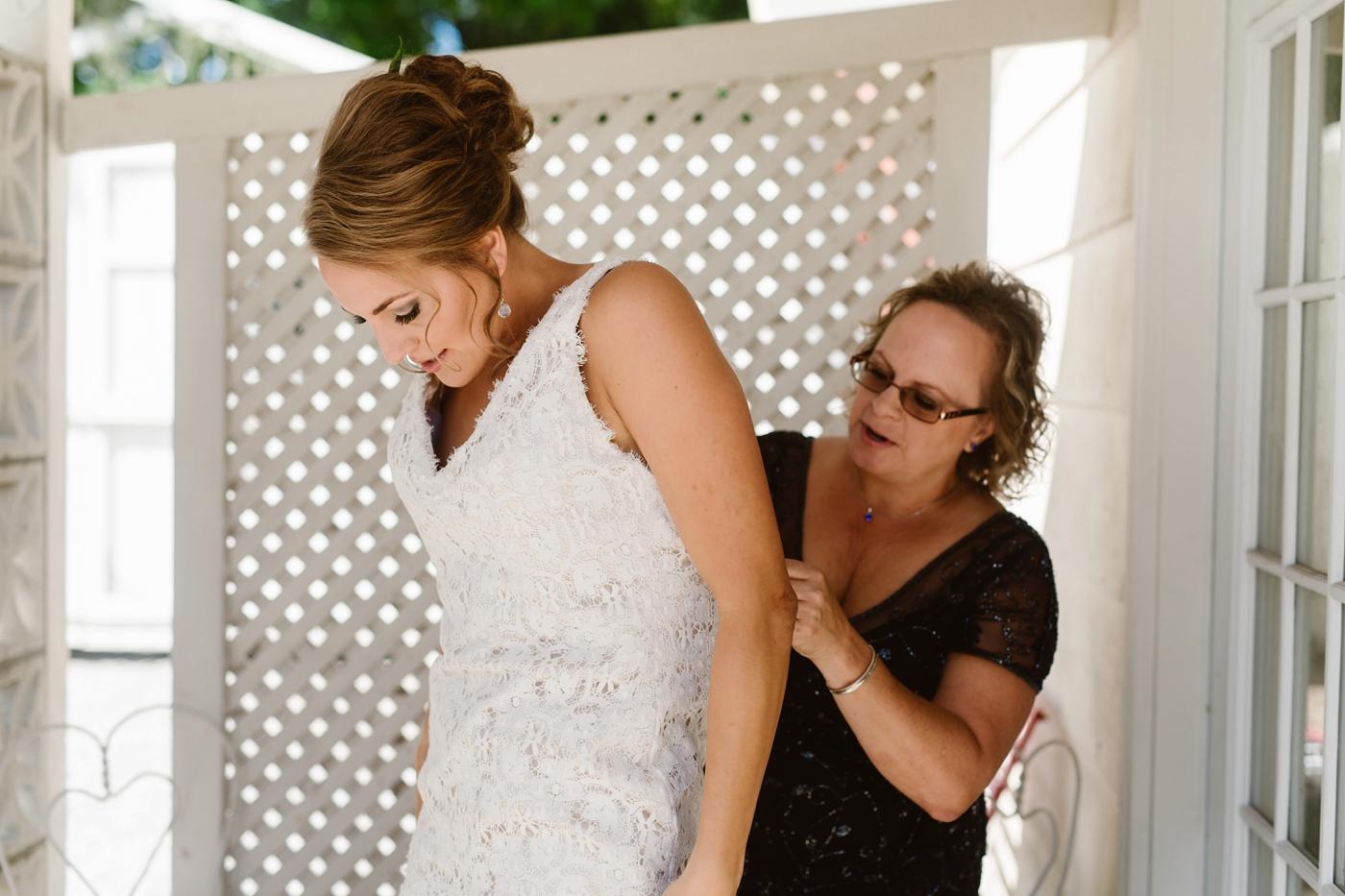 mom putting on brides dress