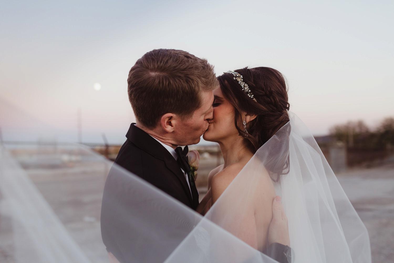 bride and groom kissing behind veil in abandoned parking garage