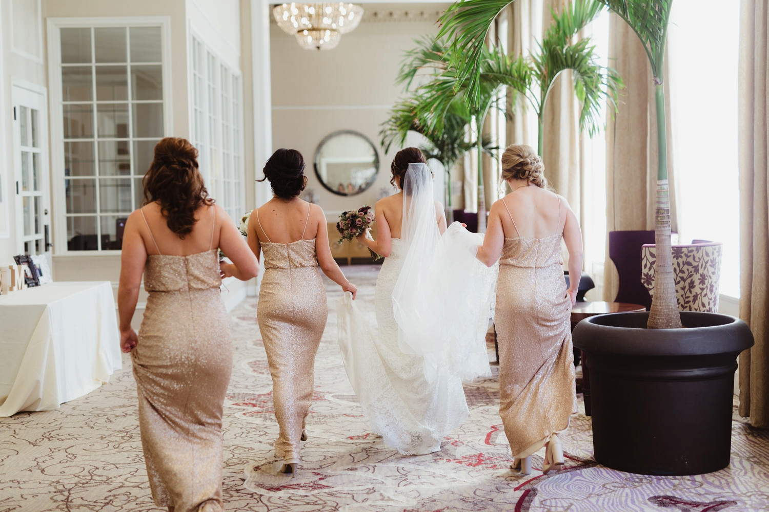 bride walking with her bridesmaids in the pere marquette hotel for her wedding