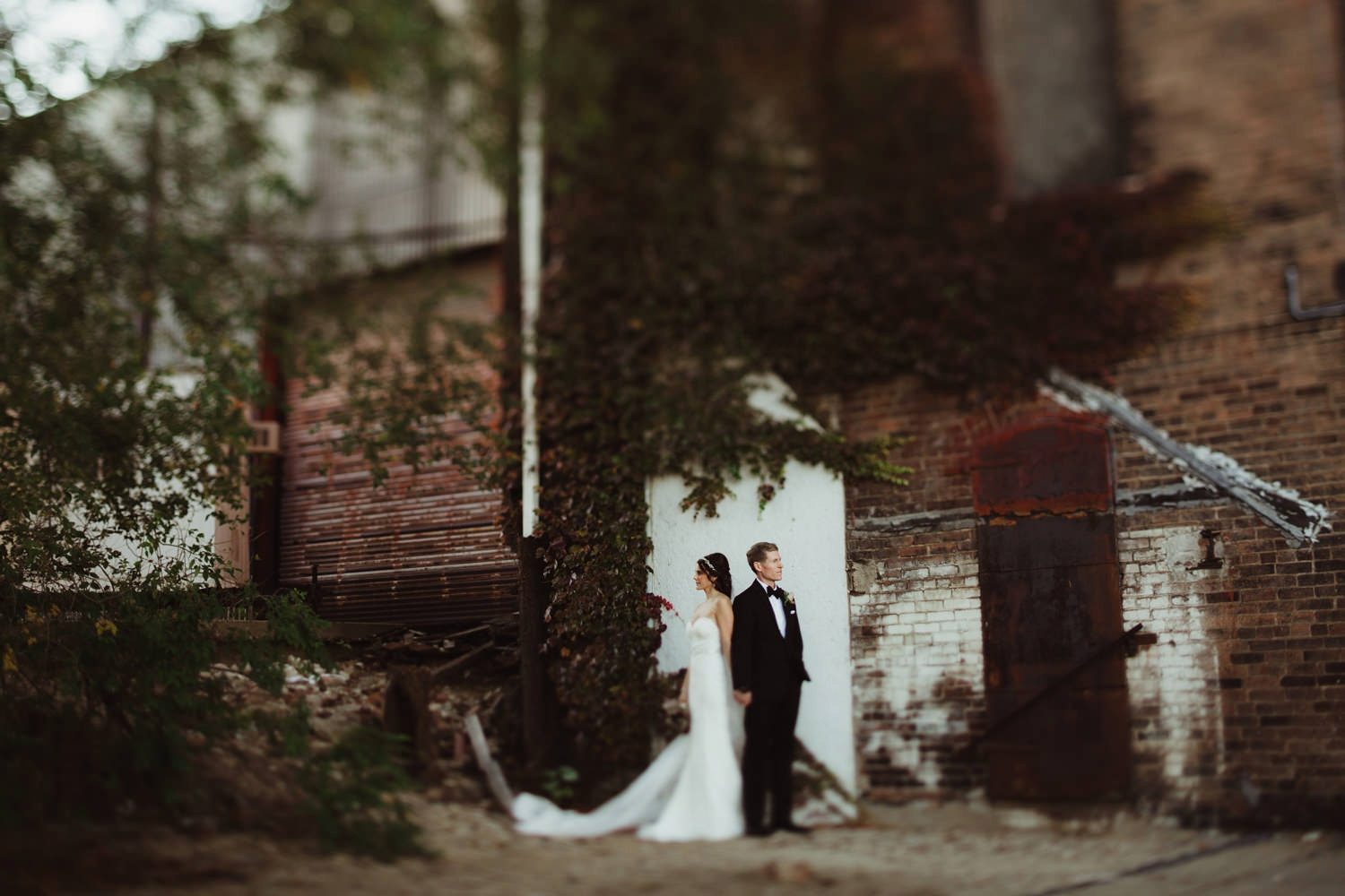bride and groom surrounded by ivey in industrial alley