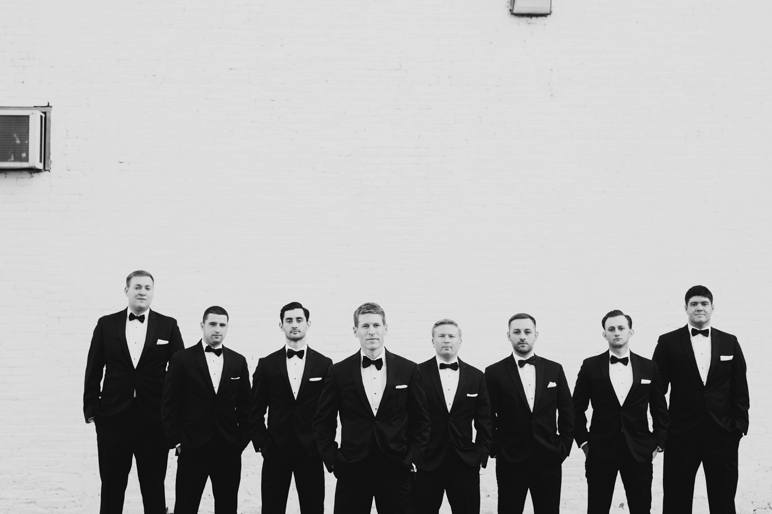 serious photo of groomsman in their tuxedos in the back alley of downtown grand rapids