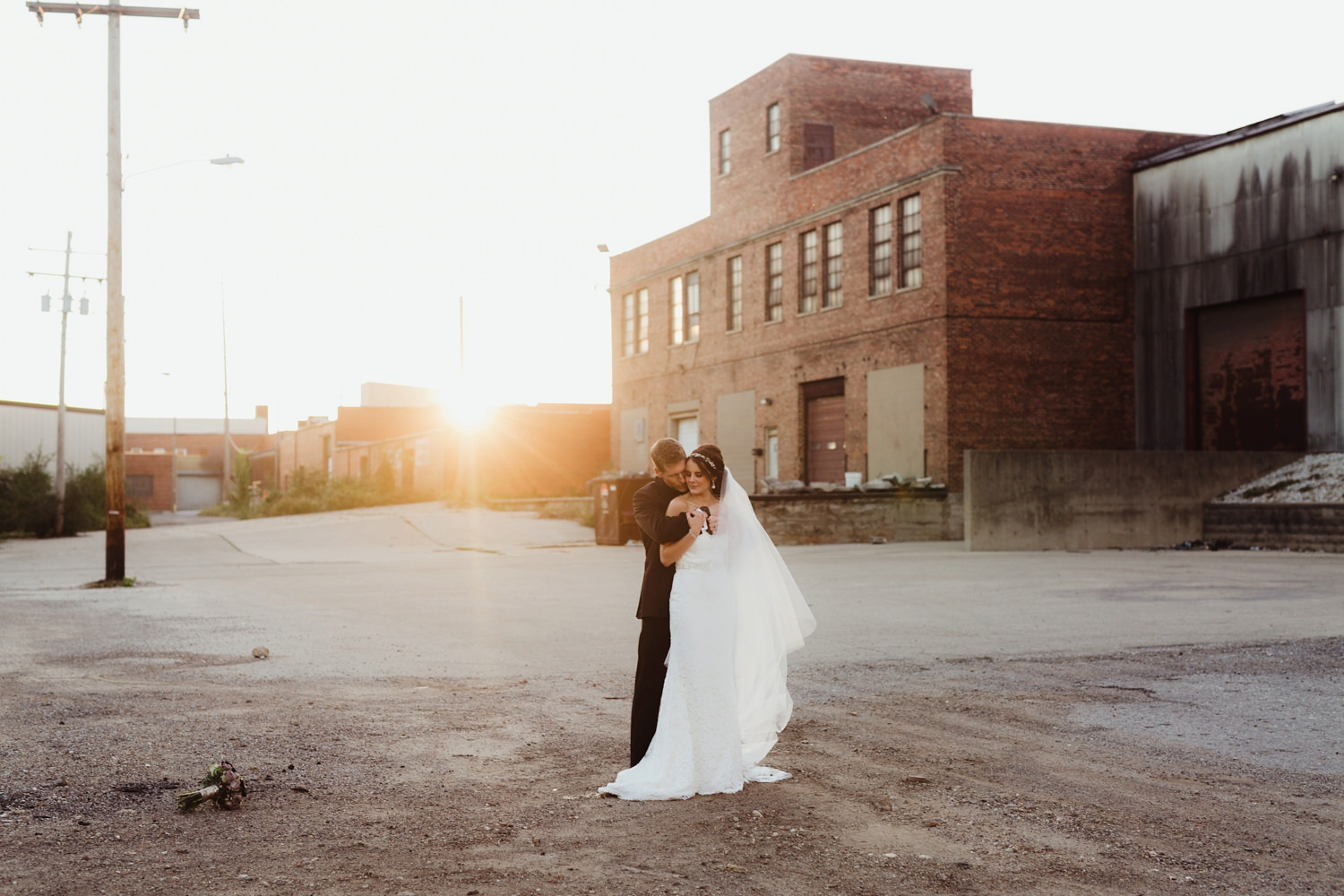 bride and groom embrasing at sunset behind a run down warehouse