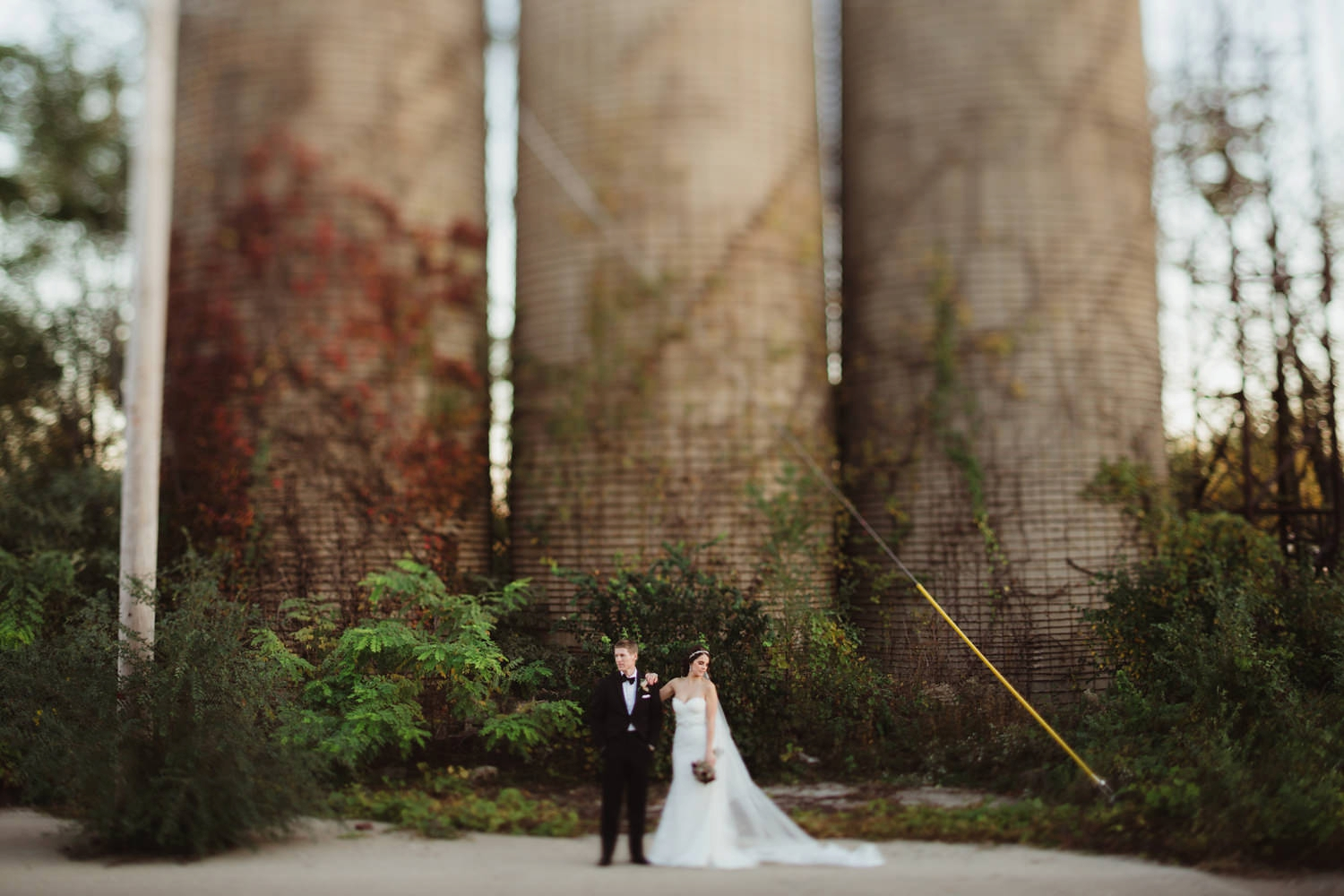 couple wedding photos in front of giant abandoned silo