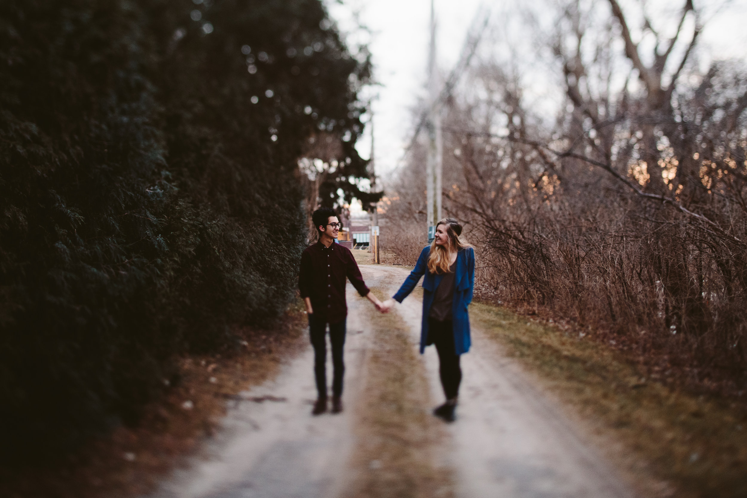 couple holding hands during northern michigan forest engagement