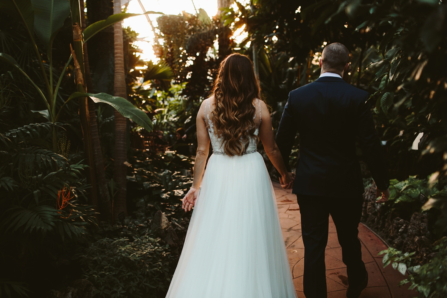 couple exiting their greenhouse elopement