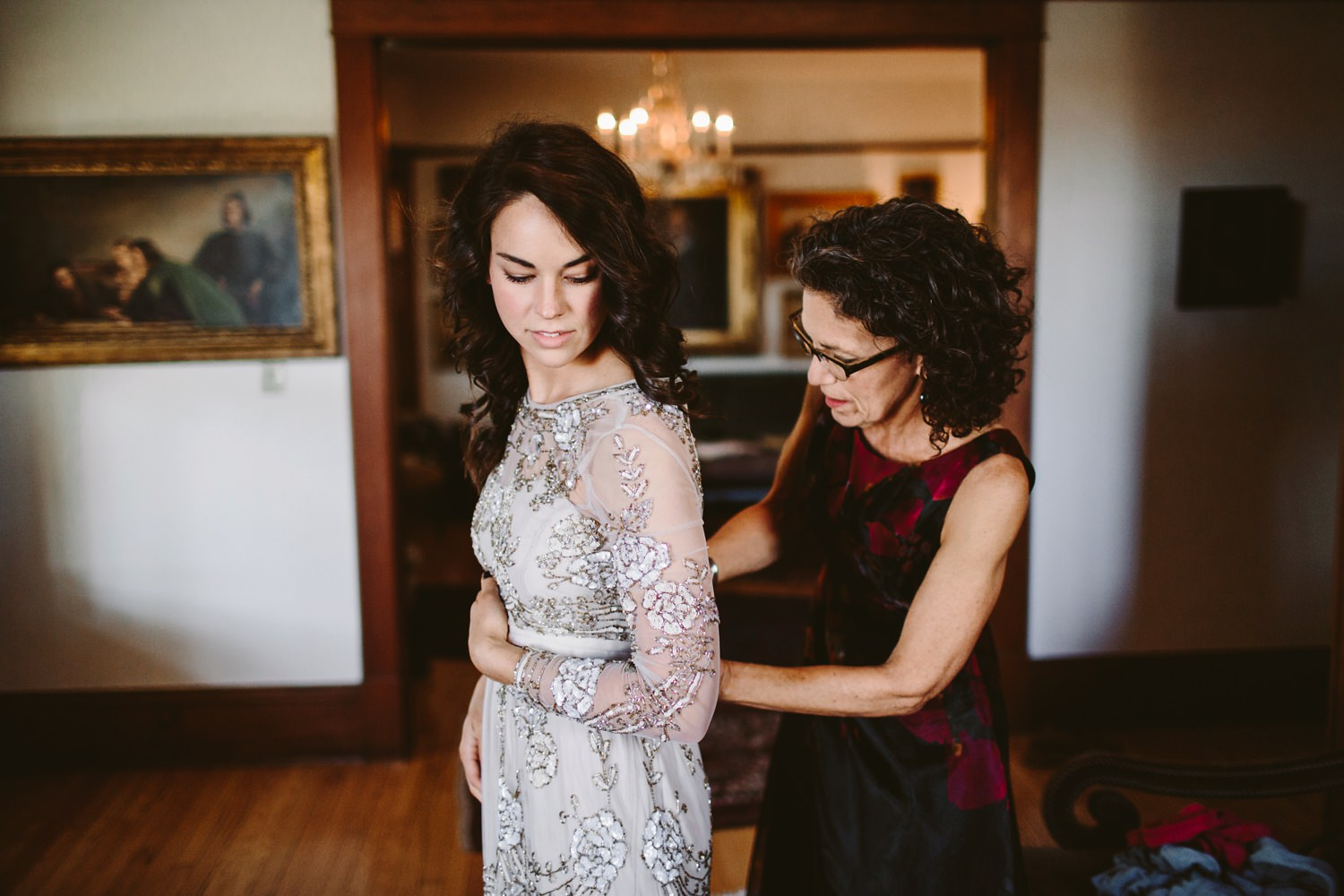 bride putting on bhldn wedding dress with mom