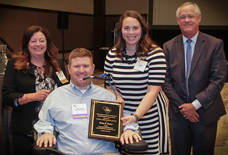 Brian Denny (second from left), accompanied by his wife Jessica, receives the 2016 Client Achievement Award from Dr. Roxzanne Breland, Chair of the SC State Agency of Vocational Rehabilitation, and Neal Getsinger (right), VR Commissioner.