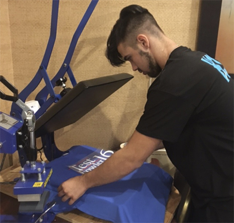 Tyler Spainhour, a junior from North Myrtle Beach High School, operates a heat press machine. Tyler has also learned to operate a Cricut machine.