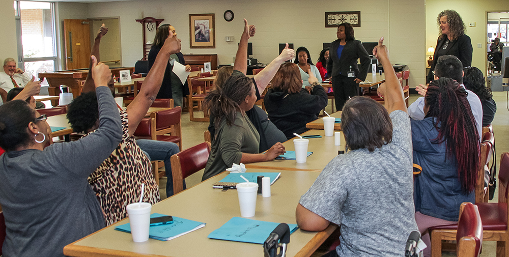 Deaf clients give their approval on the appropriateness of a model's dress during a fashion show at the Evaluation Center.