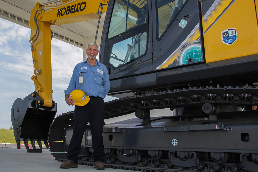 Jerald Grimes, welder, next to one the excavators produced by Kobelco in the Upstate.