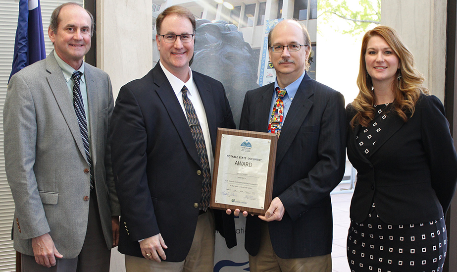 (left to right) Mark Wade, Assistant Commissioner; Matt Daugherty, Resource Specialist; and Mark Gamble, Media Resource Consultant, receiving the Notable State Document award for 2016 from Leesa Aiken, SCSL Director., March 17, 2017 at the State Library in Columbia.