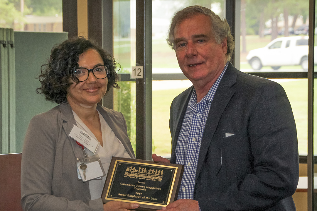 Esther Muñoz (left), counselor with the SC Vocational Rehabilitation Department and member of the Columbia Mayor's Committee on Employment of People with Disabilities, presents the Small Employer Award to Charlie Weston, owner of Guardian Fence Suppliers.