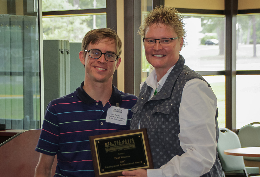 Paul Watson of Green River Log Cabins accepts the Employment Achievement Award from Amelia England, employment coach for the S.C. Vocational Rehabilitation Department, representing the Spartanburg Mayor's Committee on Employment of People with Disabilities.