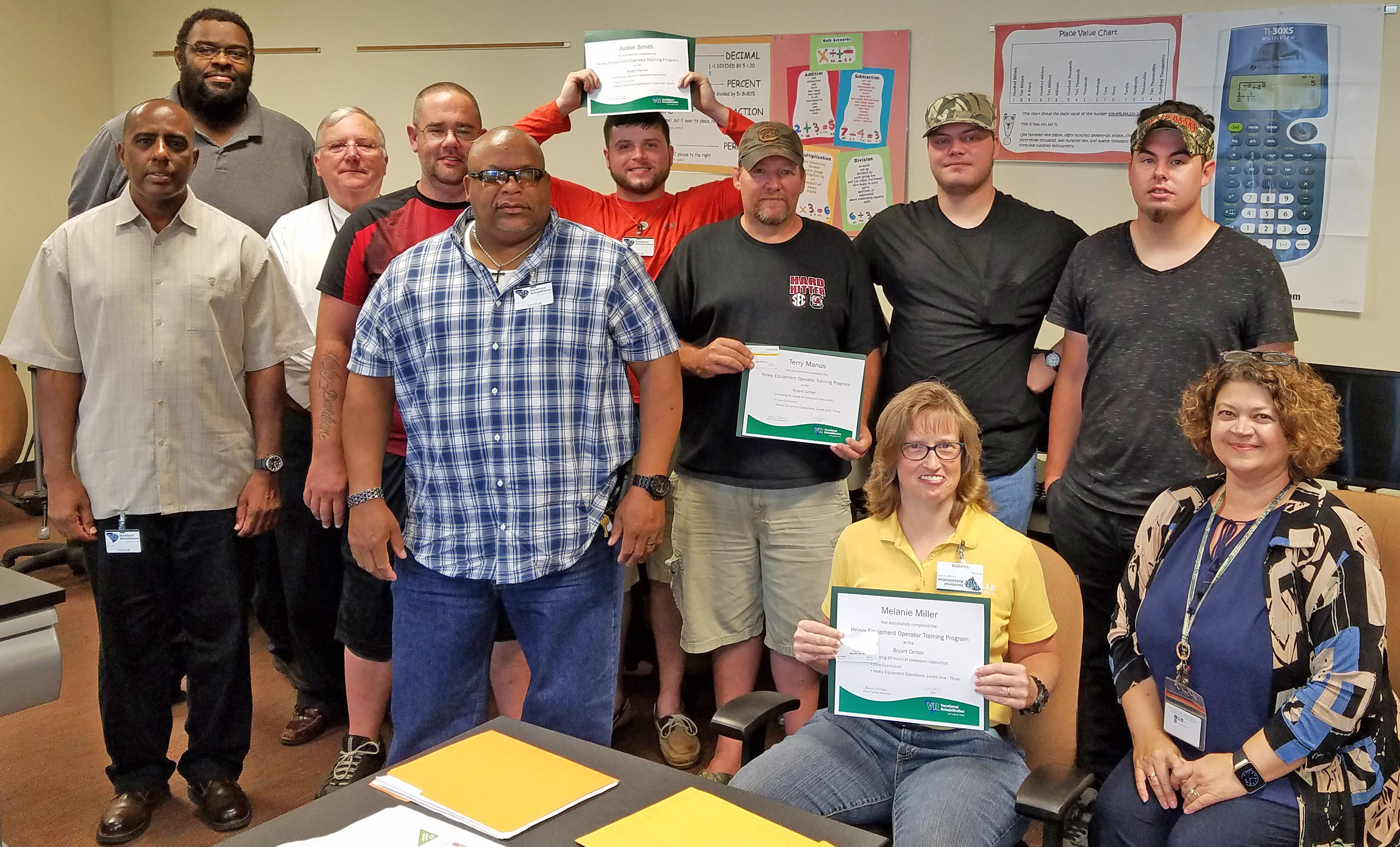 Left to right: Clients Darnell Carter and Jason Allgood; Tom McAbee, ACE/JPI; clients Paul Christoffersen and Terry Bradley; former clients Justin Smith and Terry Manus; clients Shawn Rose and Bryan Getsinger. Seated: Melanie Miller, former VR client; Jennie Thomas, Area Administrator.
