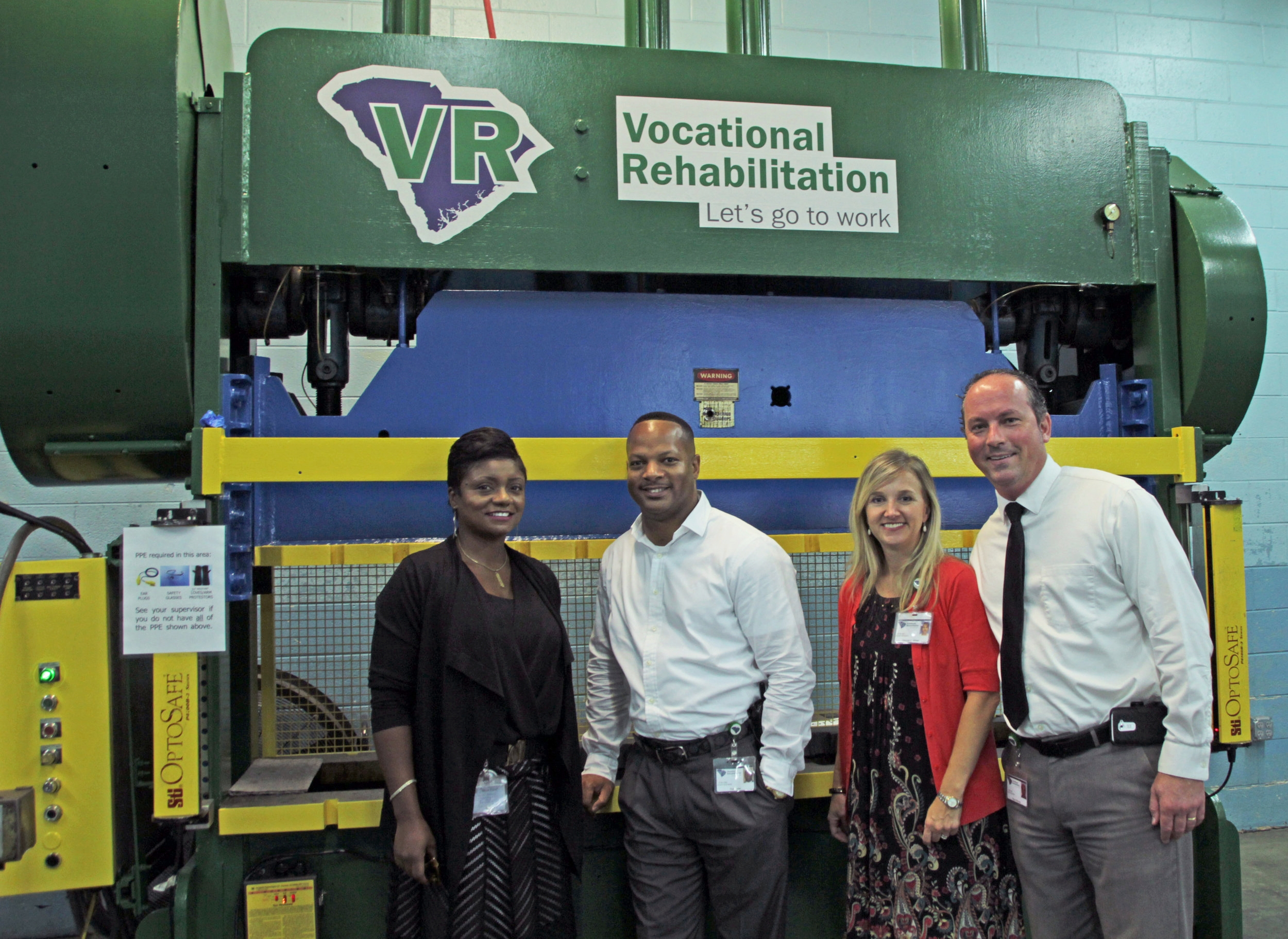 Felicia Johnson, Interim Commissioner; Tim Geter, Training Center Manager; Cole Gallman, Spartanburg Area Supervisor; and Ryan Skinner, Upstate Regional BDS, showcase the press punch machine that will be used to provide demand driven training to VR clients.