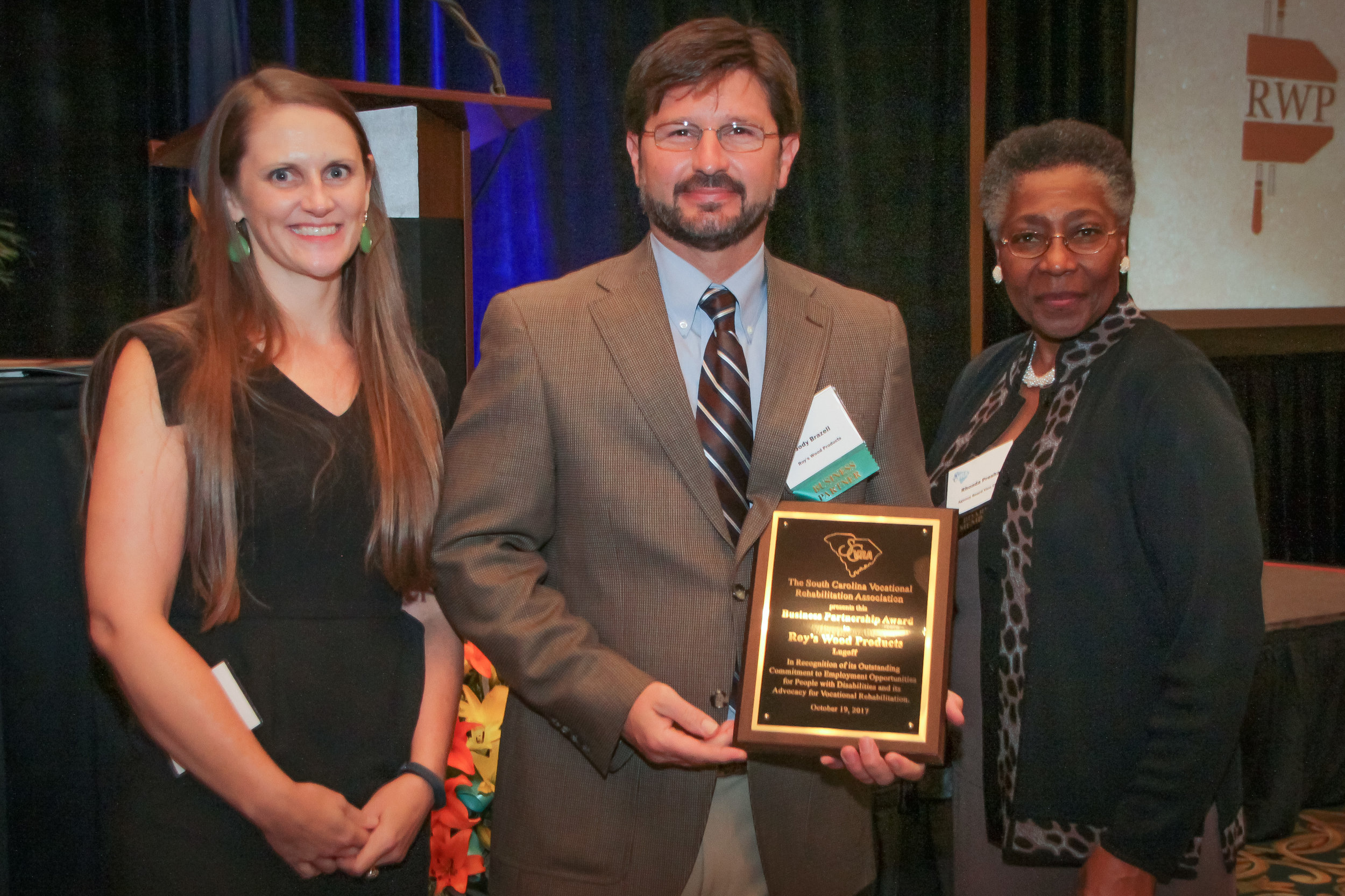 Jody Brazell (center), Co-owner of Roy's Wood Products in Lugoff, receives the SCVRA Business Partnership Award from Summer Rigby (left), Camden Area Supervisor and Rhonda Presha, Vice Chair of the SC State Agency of Vocational Rehabilitation Board.