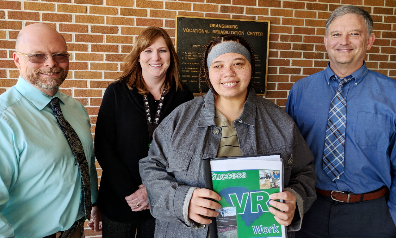 Melissa Freidman, former client, displays the book she created documenting her experiences at VR. Around her are (left to right) John Bates, Job Coach; Nicole Kilgus, Counselor; and Stephen Kesler, Vocational Assessment and Career Specialist.
