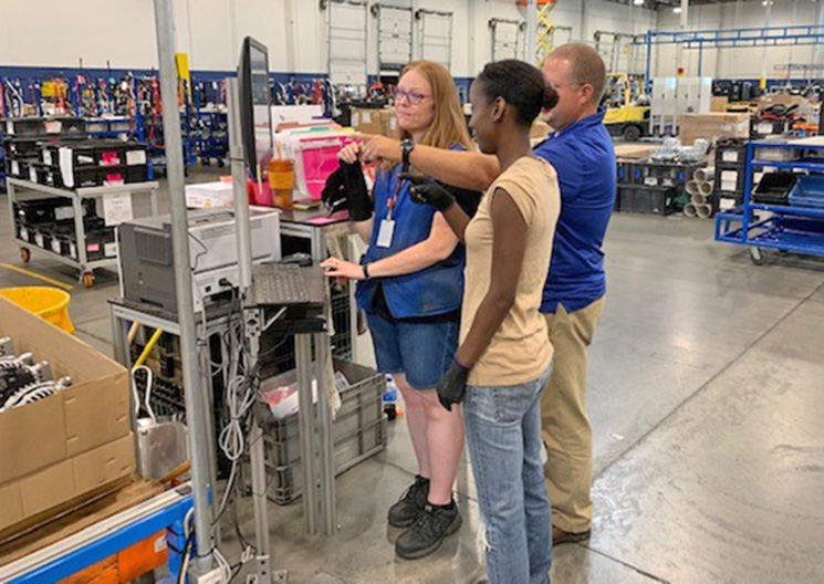 Tara Mae Jackson (left), Job Readiness Training Associate, and Shane Childers, Center Manager, give instructions to consumer Carmella Brown in the Gaffney Training Center.