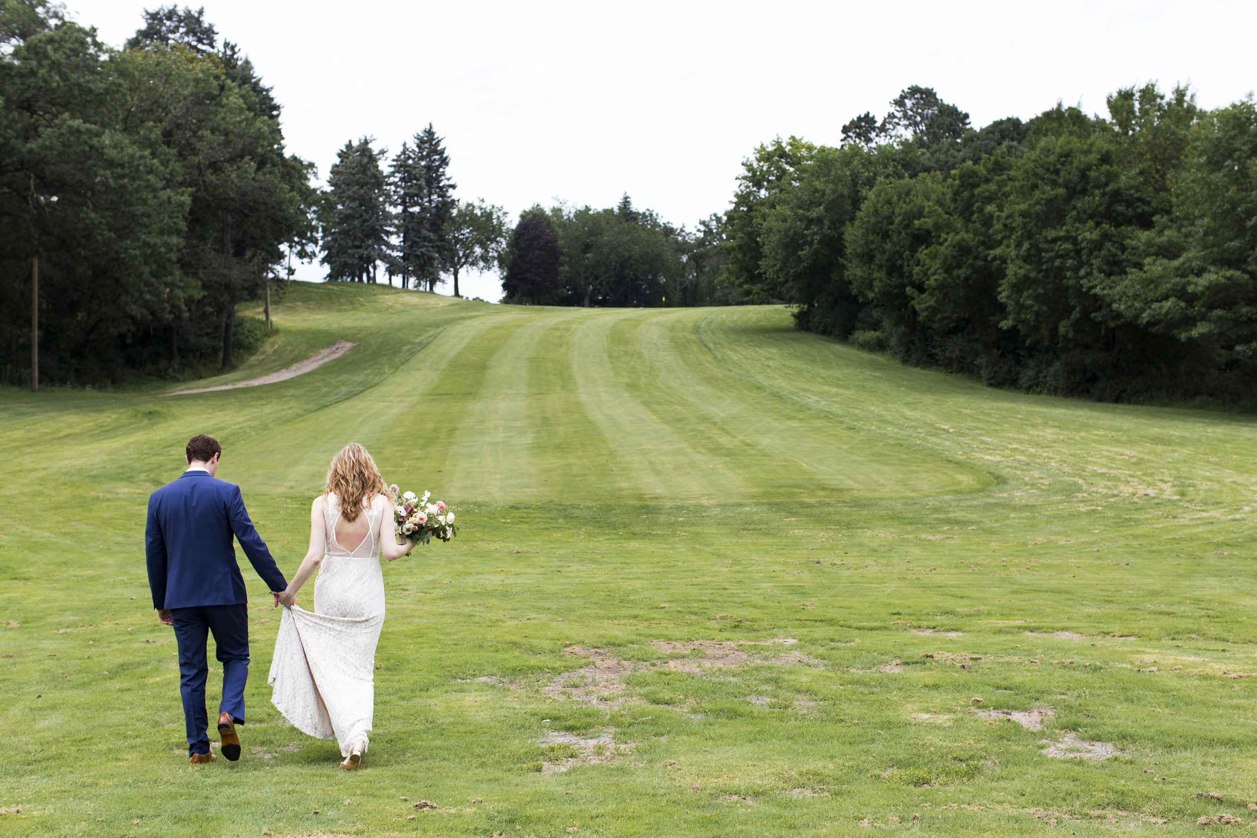 Nick holds Robin's hand as they walk out into a fairway for photos at  Theodore Wirth .  Wedding by:  Jess Ekstrand