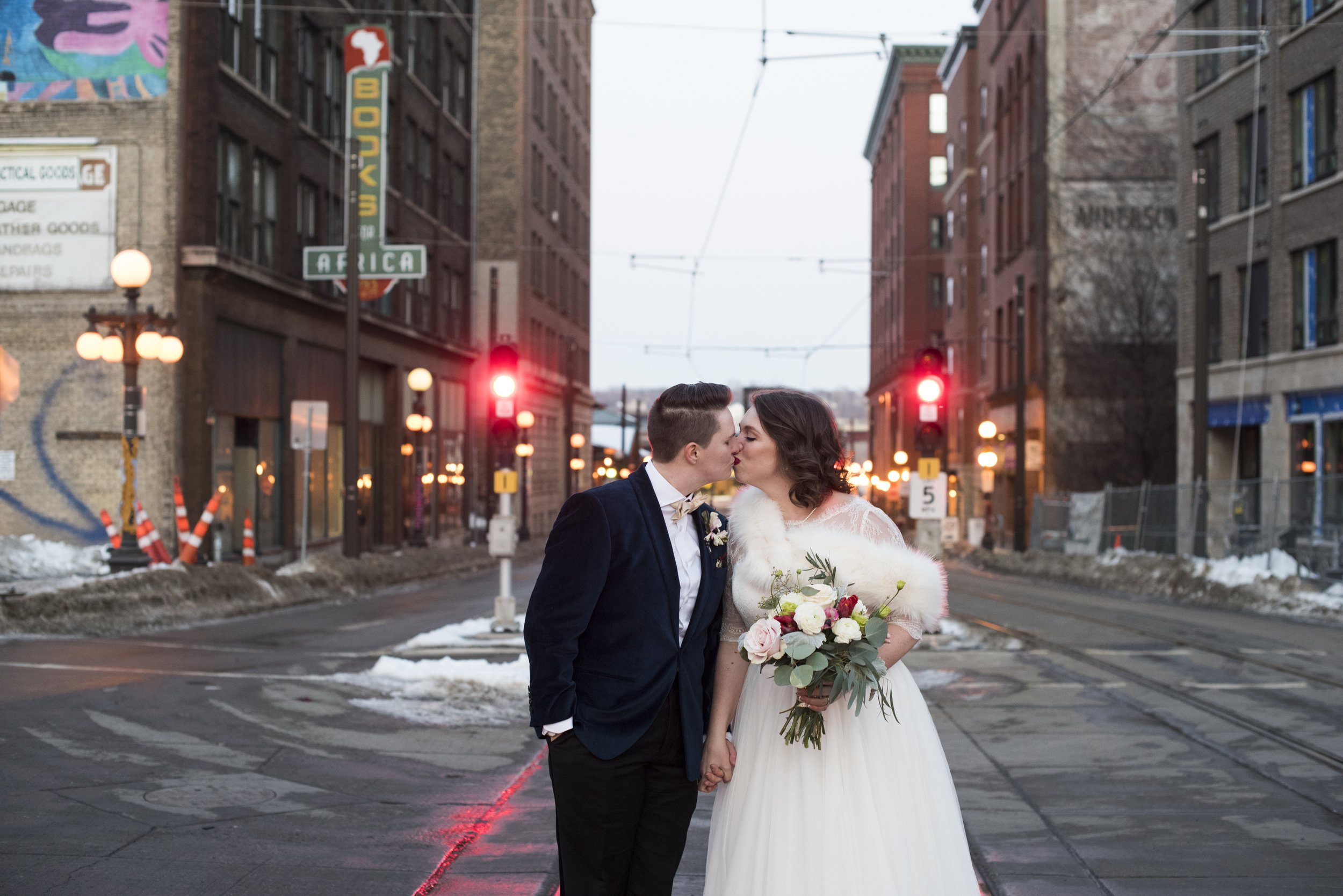 Sadie and Nora stop at the light for a kiss in downtown St. Paul.  Wedding by:  Melissa Hesse