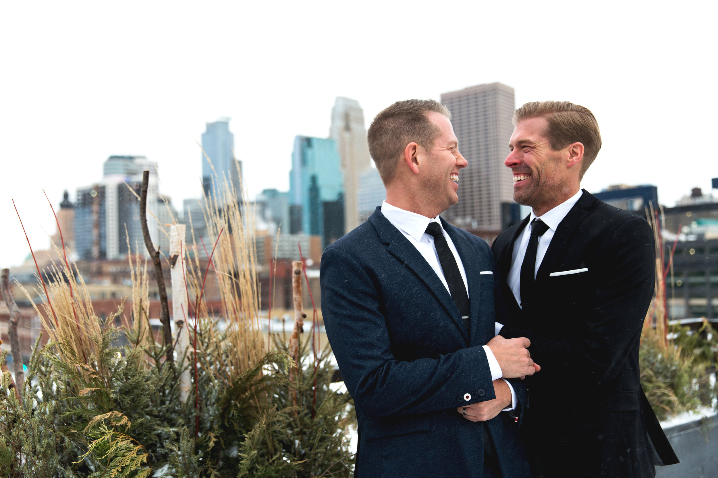 Todd and Jesse stand on the  Hewing Hotel  rooftop for photos with the Minneapolis skyline in the background.  Wedding by:  Nicole McCoy