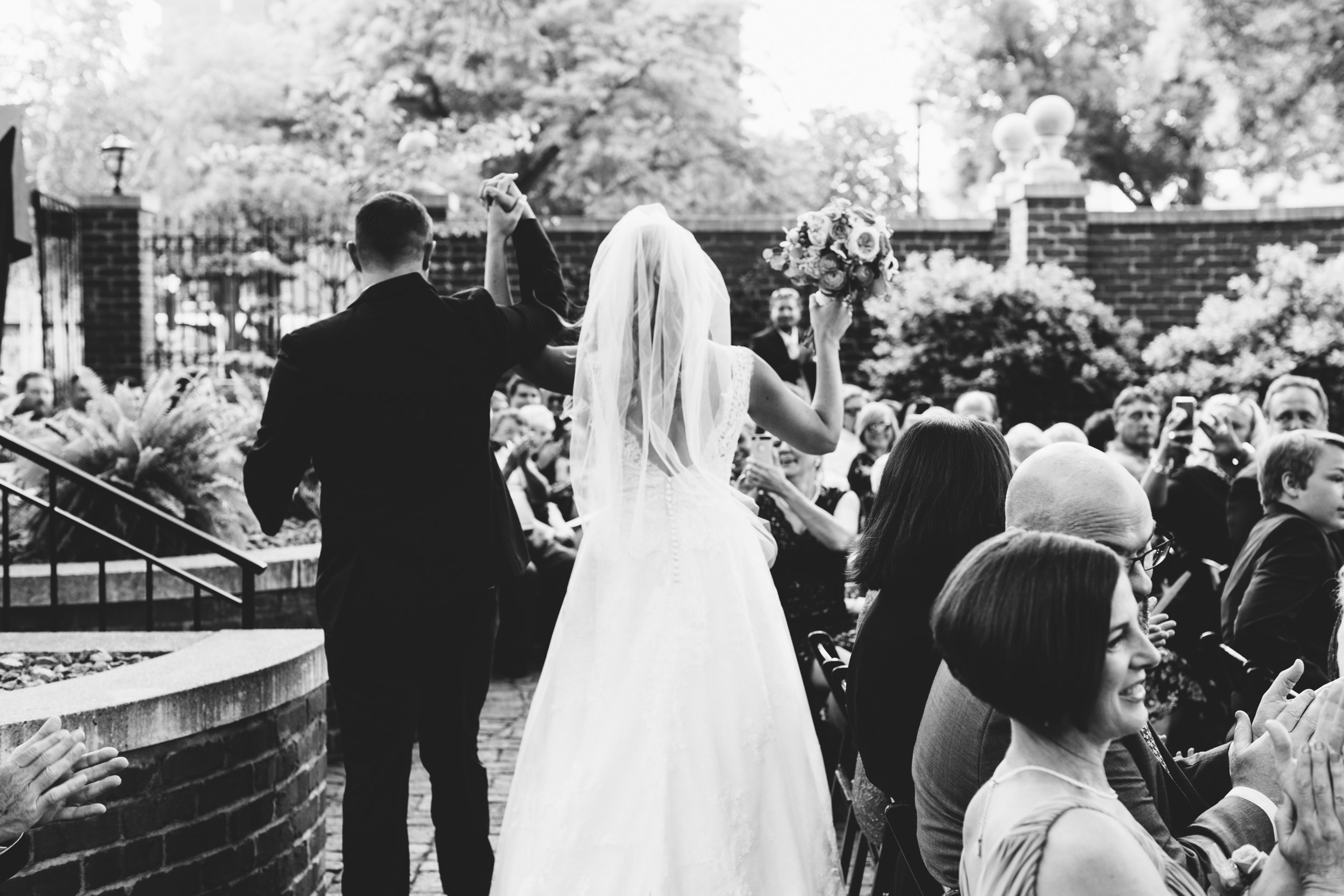 Megan and Tom throw up their arms with excitement as they walk down the aisle as newlyweds at  Minneapolis Event Centers .  Wedding by:  Jess Ekstrand