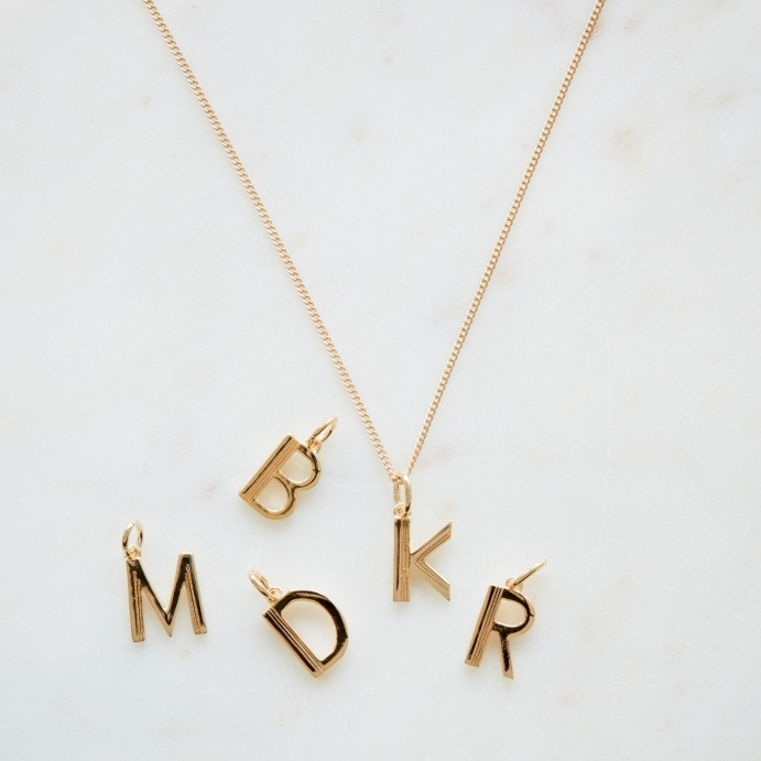 Art Deco Gold Letter Necklace - perfect for wearing the initials of little ones round your neck. Find this at Rigby & Mac and use code MAMA10 for 10% off.