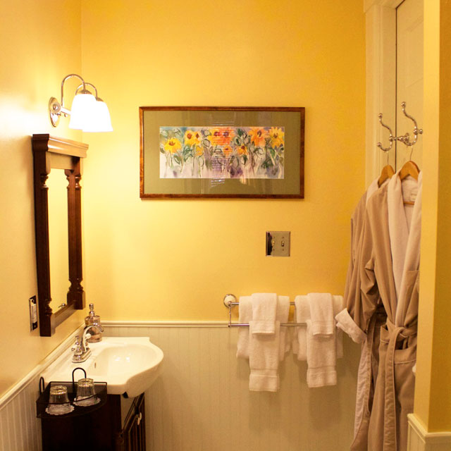 Bathroom of the conservatory room featuring plush bathrobes, porcelain sink, and shower.