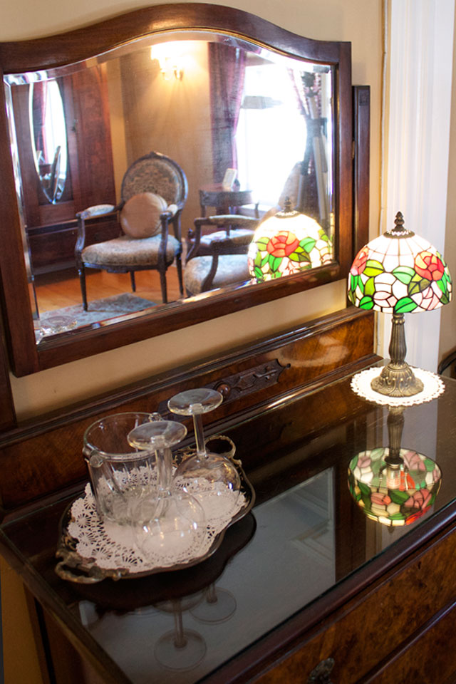 Antique dresser with mirror presents wine glasses to enjoy while at Burlington's Willard Street Inn.