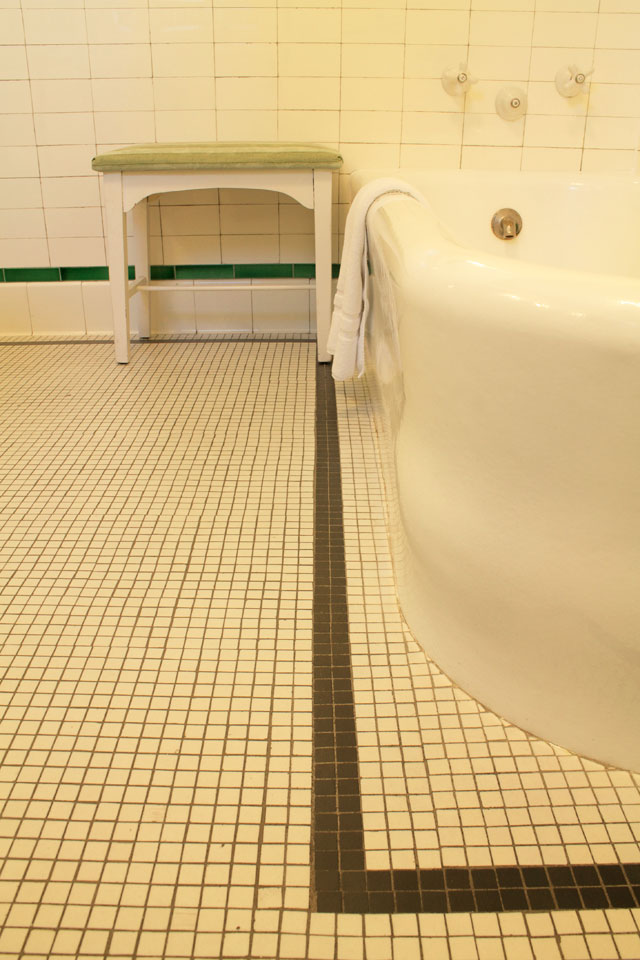 Antique tiled floor of Nantucket Room's Bath also featuring original soaking tub and tiled shower.