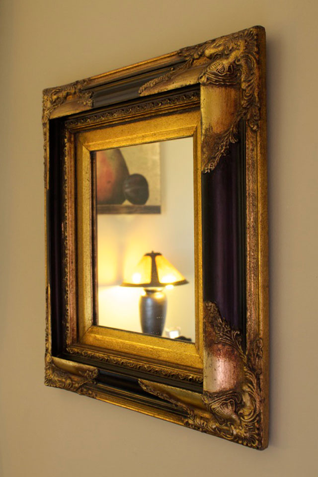 Antique black and gold mirror hung on the wall in Cobblestone Room At Willard St. Inn.